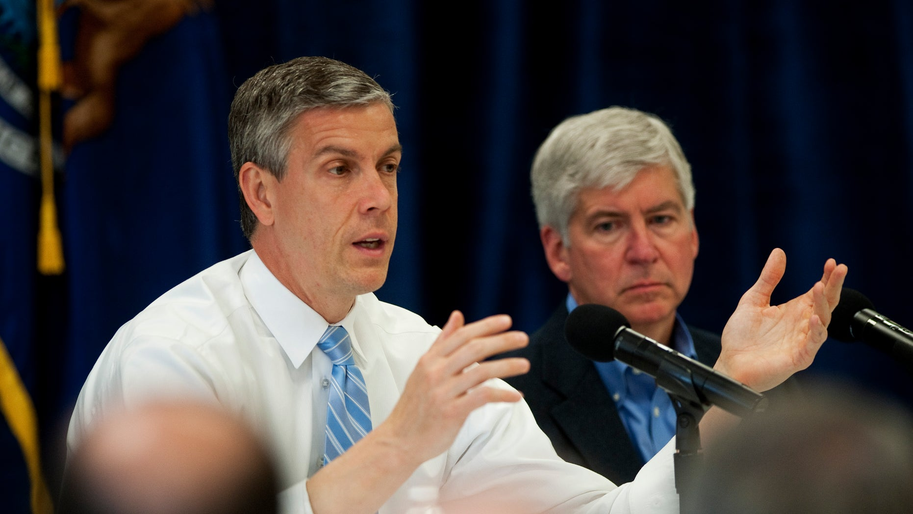 U.S. Secretary of Education Arne Duncan, left, talks to a crowd of people at Perry Child Development Center in Ypsilanti, Mich. on Monday, May 6, 2013. (AP Photo/AnnAbor.Com, Daniel Brenner)