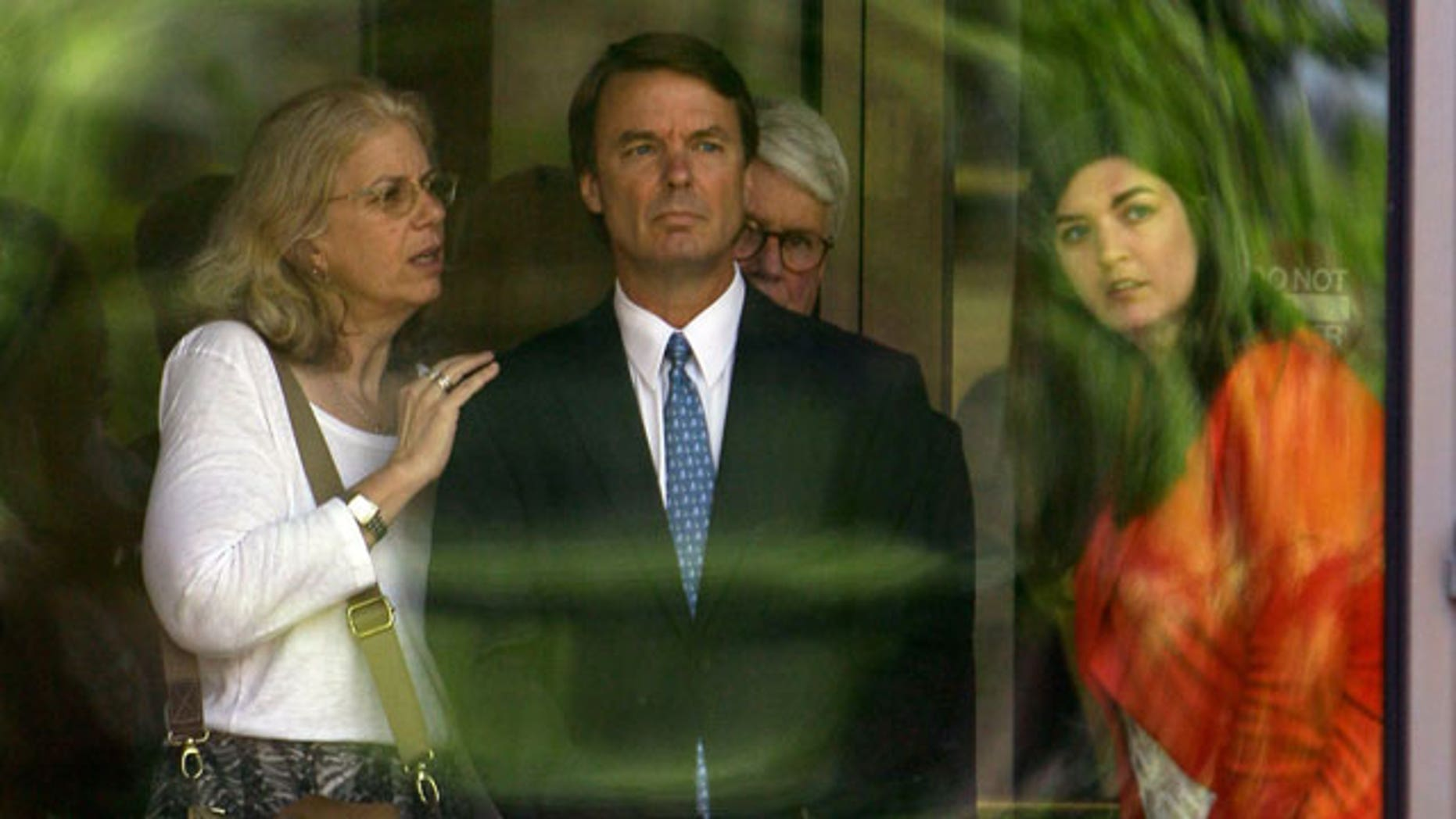 Former presidential candidate John Edwards, center, is seen with his daughter Cate, right, as they peer out of the federal building following a court appearance in Winston-Salem, N.C., Friday, June 3, 2011. (AP)
