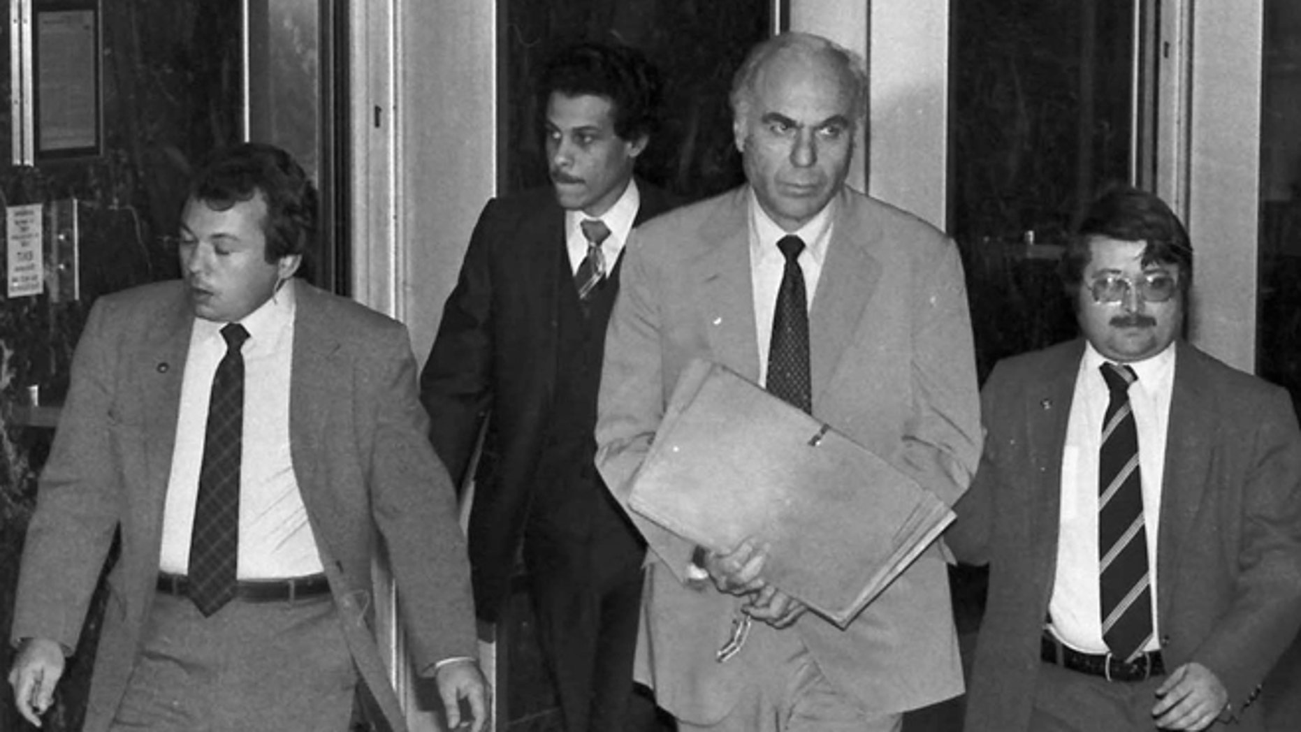 FILE - In this Jan. 22, 1983 file photo, ex-CIA agent Edwin Wilson, center, leaves federal court after a day of jury selection accompanied by U.S. Marshals in Houston.