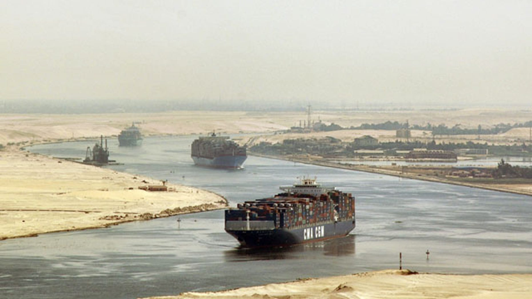In this Sept. 21, 2009 file photo, cargo ships sail through the Suez Canal, seen from a helicopter, near Ismailia, Egypt. Egypt has agreed to allow two Iranian naval vessels to transit the Suez Canal to the Mediterranean.