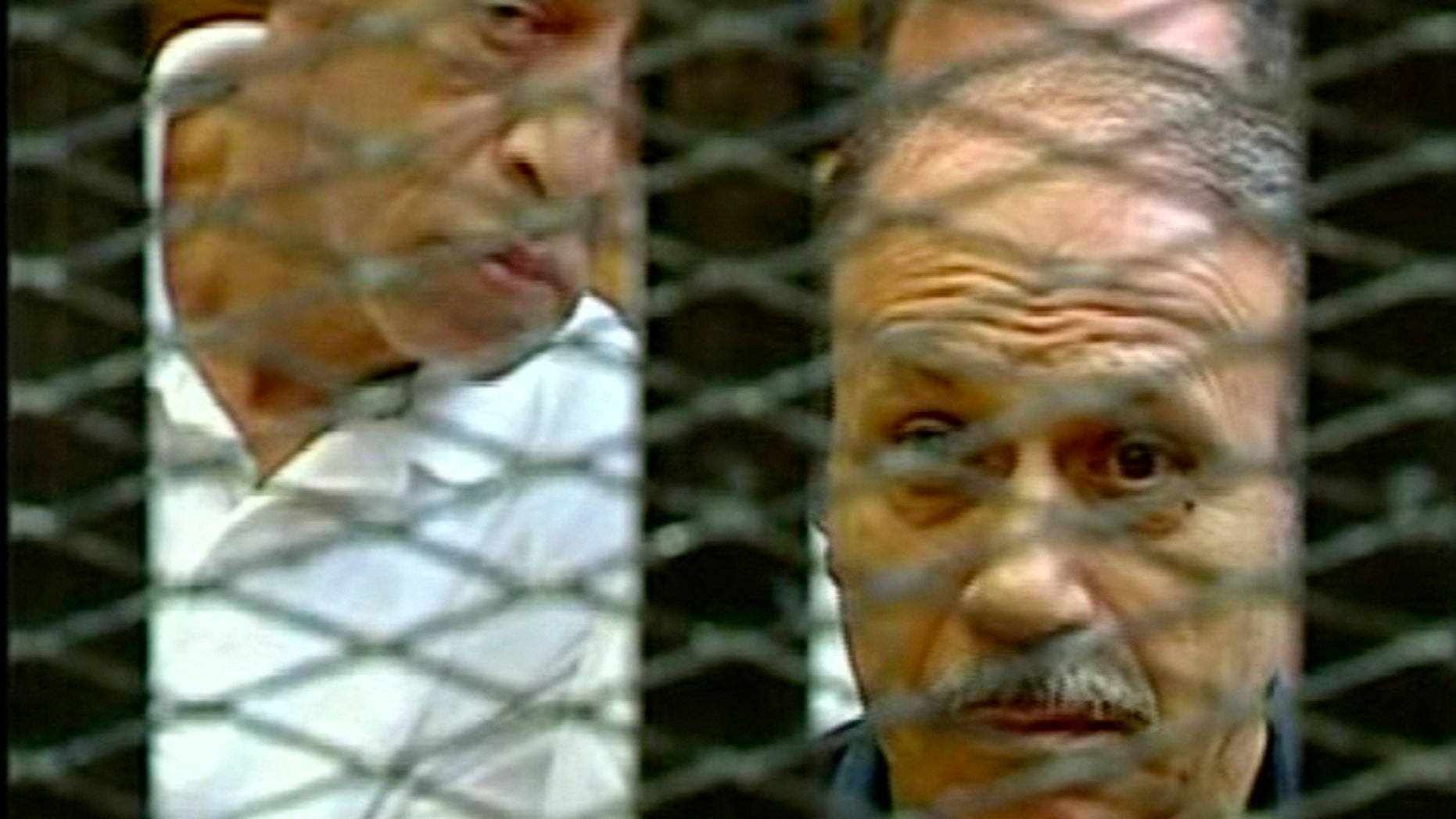 Egyptian Interior Minister Habib el-Adly, right, in a cage of mesh and iron bars during his trial in a Cairo courtroom Thursday Aug. 4, 2011.