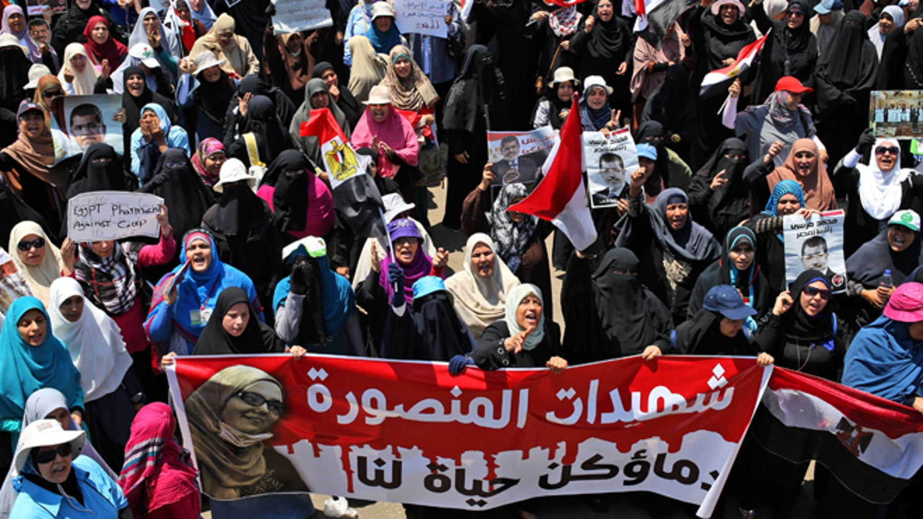 """July 21, 2013: Supporters of ousted Egyptian President Mohammed Morsi carry a banner with Arabic words that reads, """"Martyrs of Mansoura, your bloods is life for us,"""" depicting a woman who was killed during a recent protest, as they attend a demonstration in front of the National Council for Human Right building in Cairo, Egypt."""