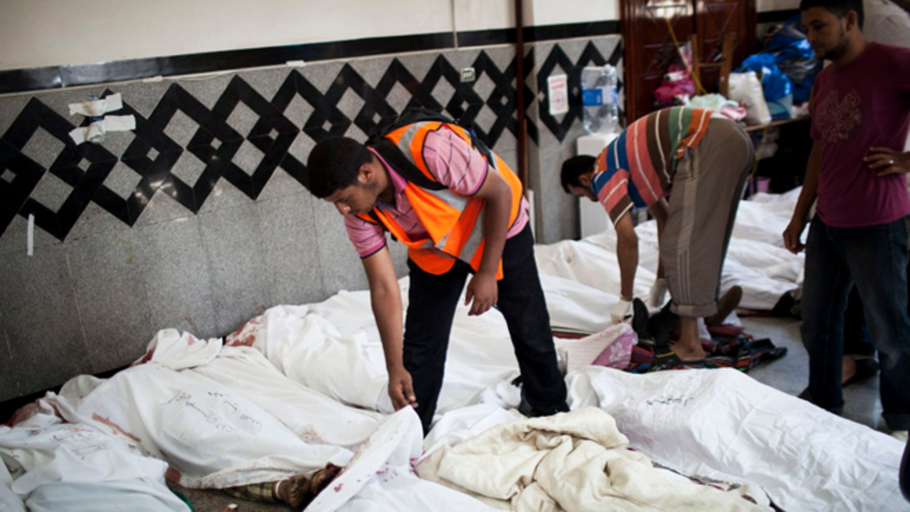 July 27, 2013: An Egyptian doctor identifies the body of a supporter of Egypt's ousted President Mohammed Morsi killed in clashes with security forces at Nasr City, where pro-Morsi protesters have held a weeks-long sit-in, in a field hospital in Cairo, Egypt.