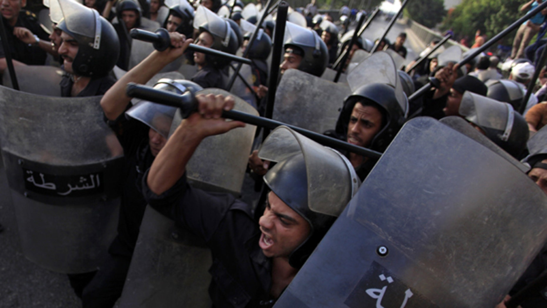 June 11, 2013: Egyptian riot police try to separate Salafis and protesters during clashes in front of the Culture Ministry in Cairo, Egypt.