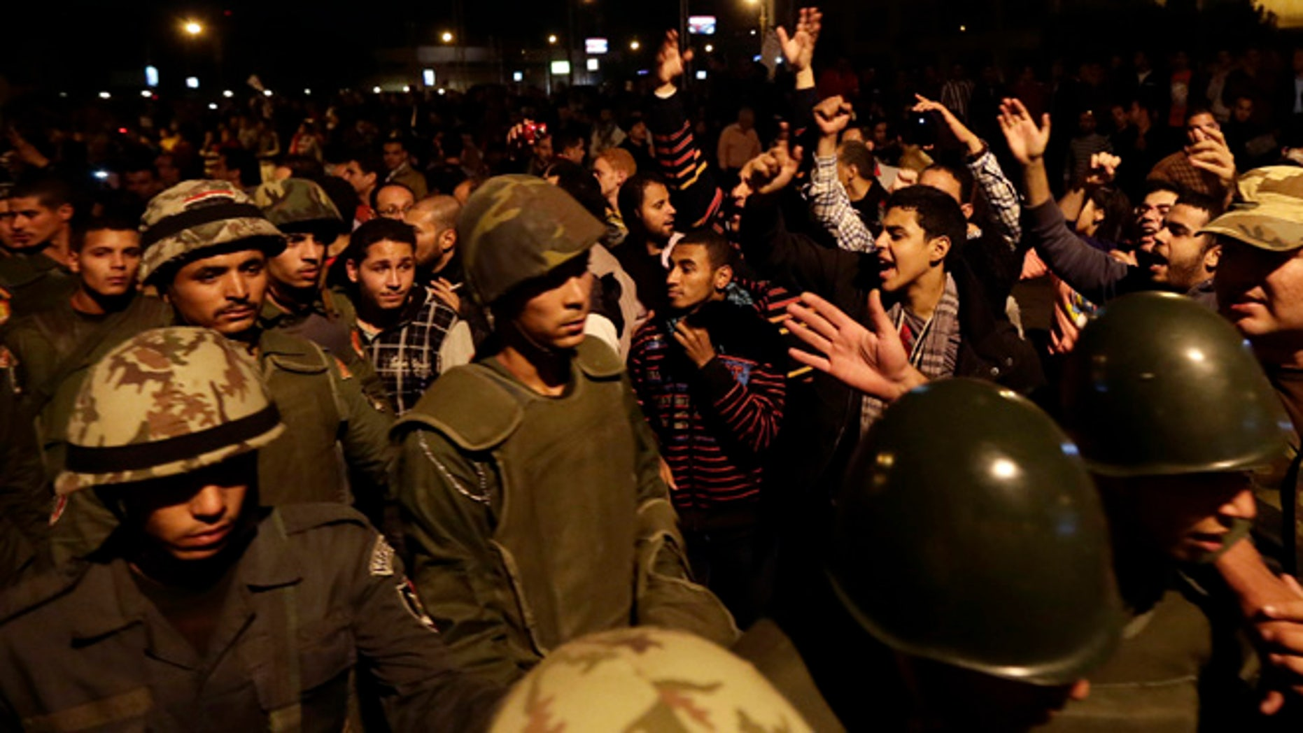 Dec. 7, 2012: Egyptian protesters salute Egyptian army soldiers as they leave their position outside the presidential palace, in Cairo, Egypt.