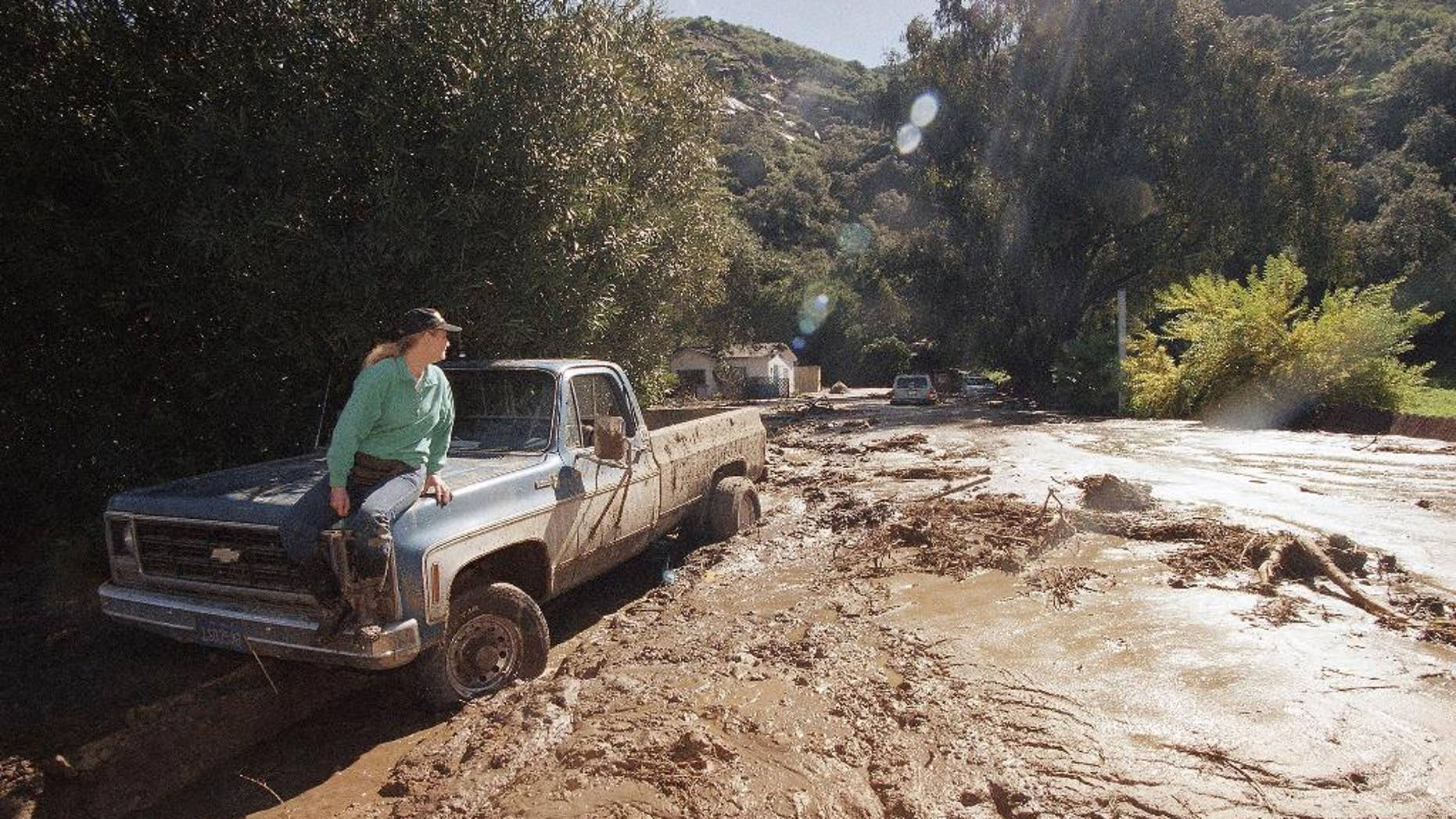 FILE - In this Feb. 24, 1998 file photo, a woman waits for a tow truck on the hood of her brother's pickup after a wall of mud plowed down Laguna Beach Canyon Road in Orange County, Calif. forcing her to evacuate her home, in background. A long anticipated El Nino weather warping is finally here. But for drought-struck California, it's too little, too late, meteorologists say. The National Weather Service Thursday proclaimed the somewhat infamous weather phenomenon El Nino is now in place. It's a warming of a certain patch of the central Pacific that changes weather patterns worldwide, associated with flooding in some places, droughts elsewhere, a generally warmer globe, and fewer Atlantic hurricanes. El Ninos are usually so important that economists even track it because of how it affects commodities. This year's El Nino that has arrived isn't big and is late so it's unlikely to do much to alleviate the current California drought. (AP Photo/Nick Ut, File)