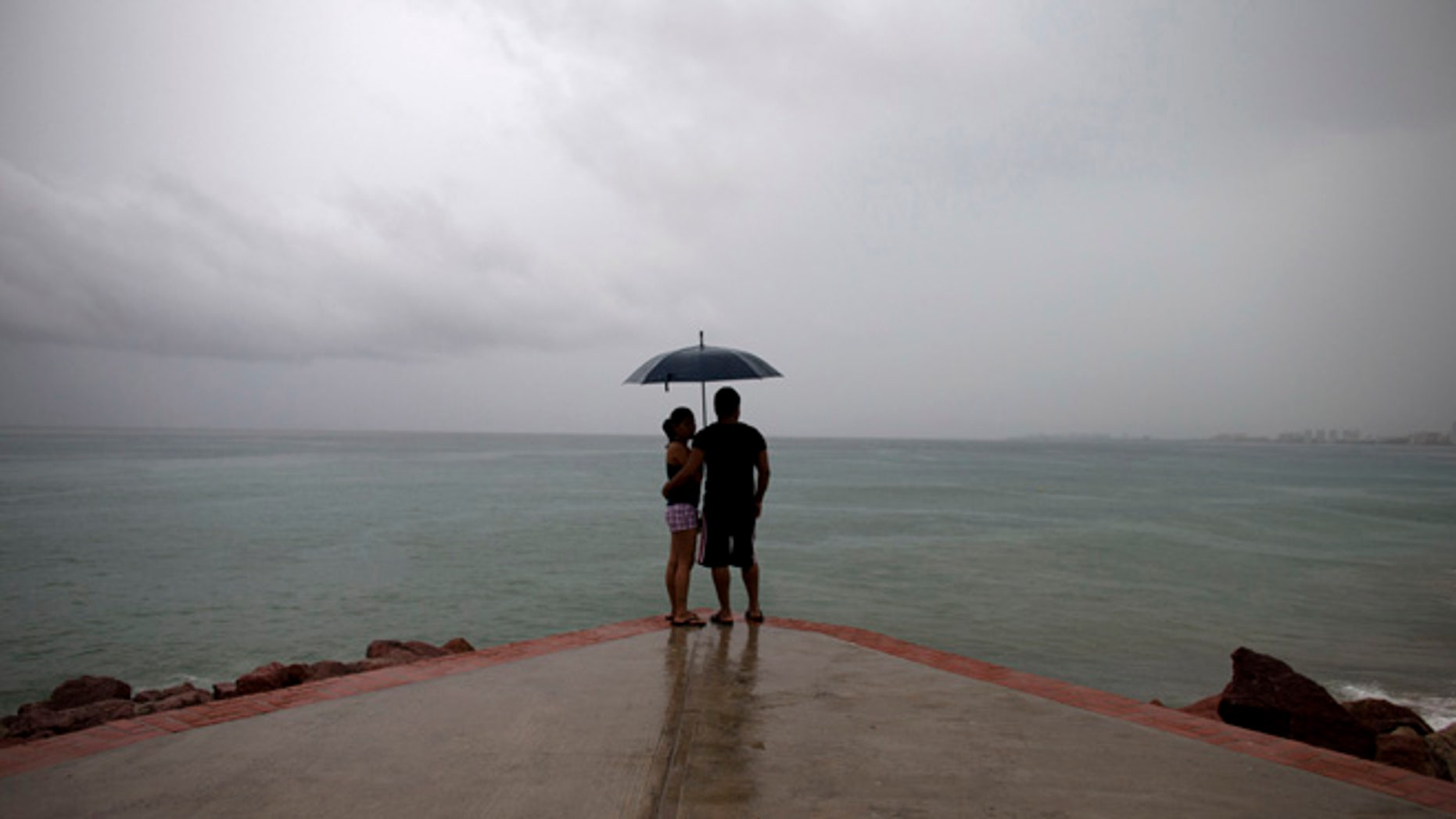 "FILE - In this Friday, Oct. 23, 2015, file photo, a couple looks out to sea as rainfall increases with the approach of Hurricane Patricia in Puerto Vallarta, Mexico. Mexico weathered a record eastern Pacific hurricane season with almost no deaths and relatively little damage, given the intensity of this year's storms. According to the U.S. National Oceanic and Atmospheric Administration's 2015 hurricane season report released Tuesday, Dec. 1, 2015, Patricia was ""the strongest hurricane on record in the Western Hemisphere"" just before it struck a sparsely populated stretch of Mexico's Pacific coast. (AP Photo/Rebecca Blackwell, File)"