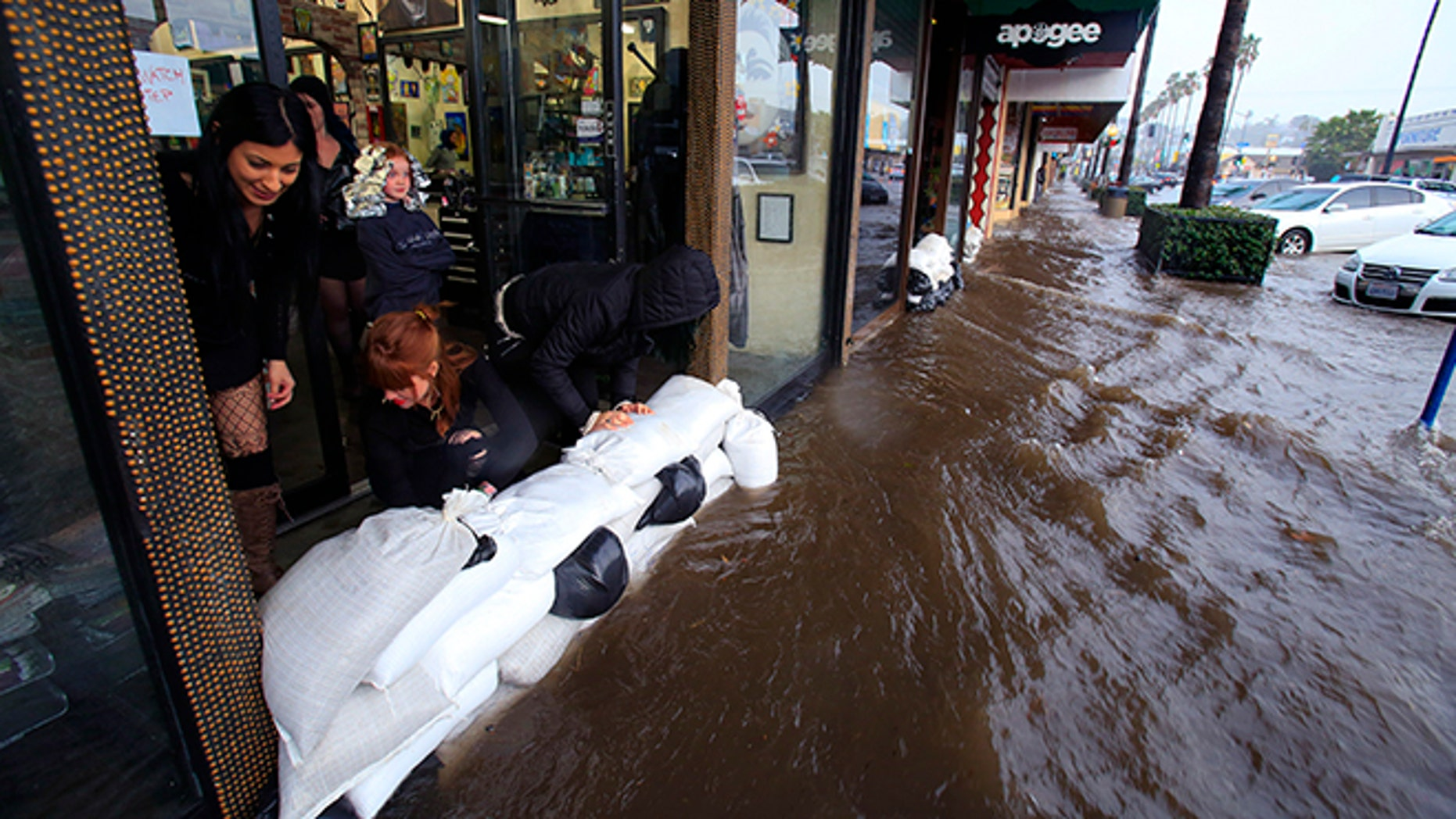 From left, Amanda Bourbois, Mary Spear and Jordan Brown place sand bags in front of the Electric Chair salon Wednesday, Jan. 6, 2016, in San Diego. El Nino storms lined up in the Pacific, promising to drench parts of the West for more than two weeks and increasing fears of mudslides and flash floods in regions stripped bare by wildfires. (Nelvin C. Cepeda/The San Diego Union-Tribune via AP)  NO SALES; MANDATORY CREDIT