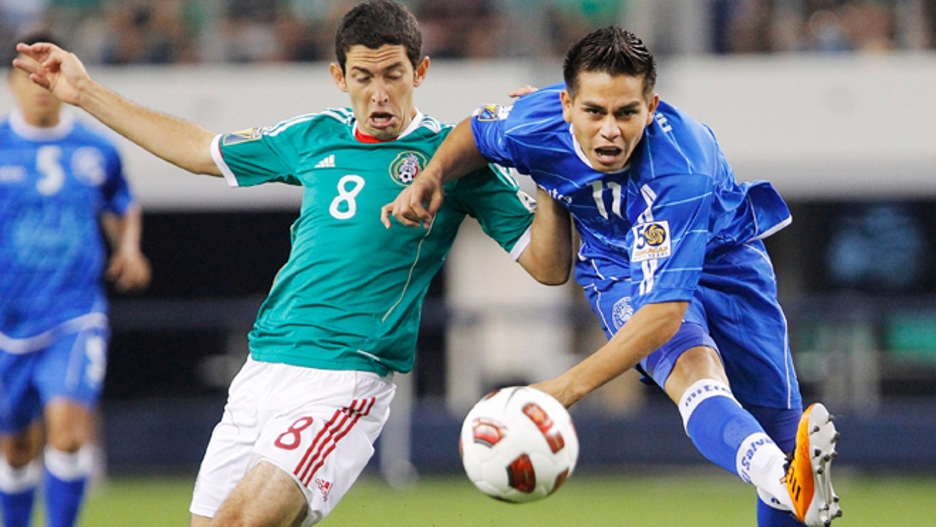 FILE - In this June 5, 2011 file photo, Mexico's Israel Castro, left, and El Salvador's Rodolfo Zelaya fight for the ball during the first half a CONCACAF Gold Cup soccer match at Cowboys Stadium in Arlington, Texas. El Salvador's football federation announced on Wednesday, Aug. 21, 2013 it has suspended 22 of their players, included Zelaya, in an investigation into alleged match-fixing in games by the national team from 2010 to 2012. (AP Photo/Brandon Wade, File)