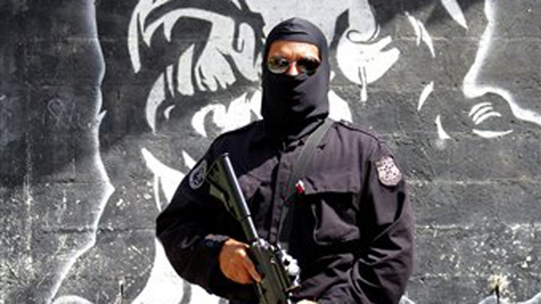 In this April 5, 2016 photo, a masked and armed policeman patrols a gang controlled neighborhood in San Salvador, El Salvador. Hyper-violent gangs declared open-season on police in this Central American nation in response to a government crackdown that began last year. In just three weeks in January, gang members were blamed in the slayings of a cop's father, a soldier's brother, the wives of two police officers and a woman and her son who were relatives of a cop. (AP Photo/Alex Peña)