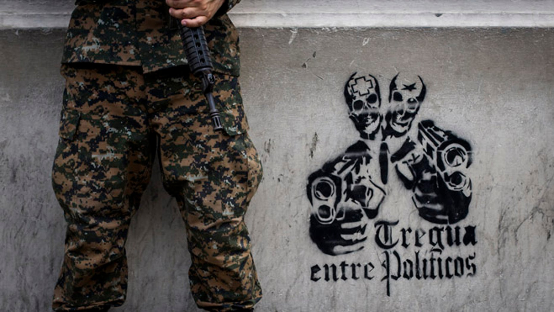 """In this June 14, 2016 photo, a soldier stands next to a stenciled graffiti that reads in Spanish """"Truce between politicians"""" painted on the main walls of the National Palace in San Salvador, El Salvador. After becoming the world's murder capital last year and posting an equally bloody start to 2016, El Salvador has seen its monthly homicide rates fall by about half. The government attributes the drop to a tough military crackdown on the country's powerful gangs, while the gangs themselves claim credit for a nonaggression pact between the three biggest criminal groups. (AP Photo/Salvador Melendez)"""