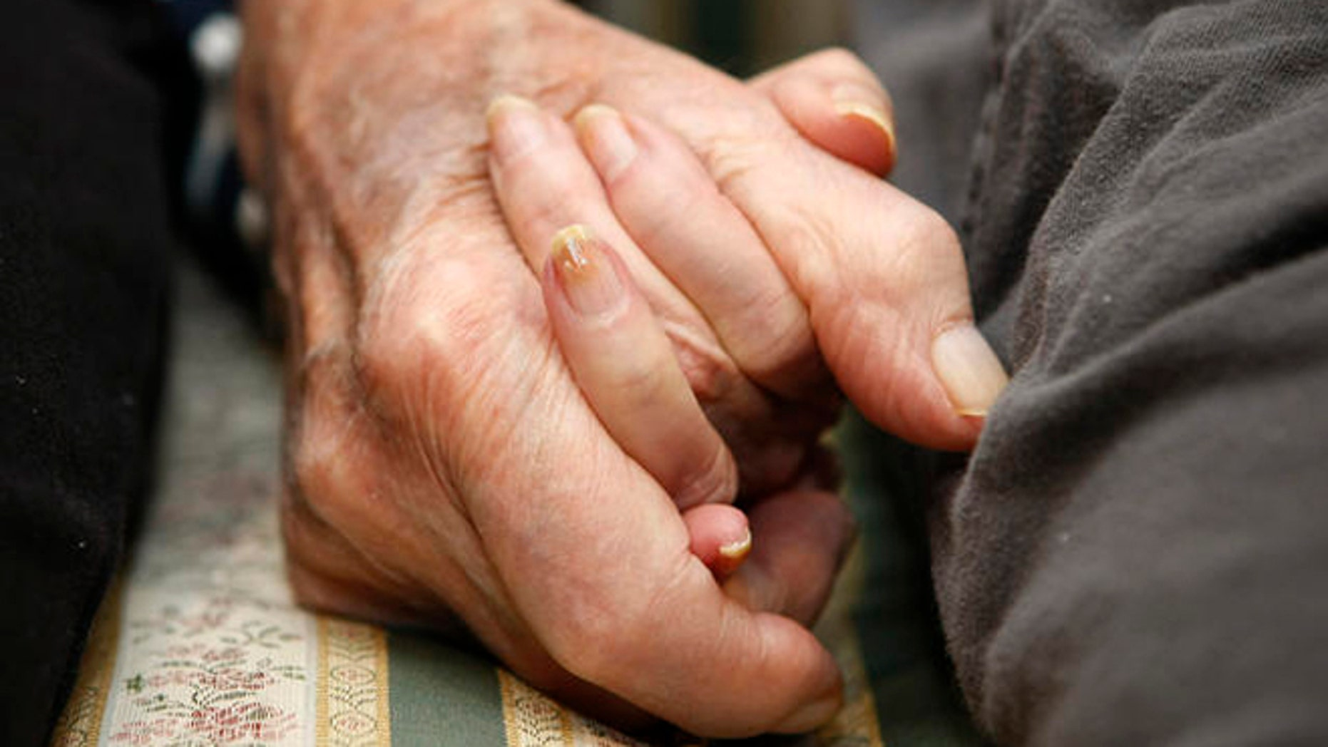 **HOLD FOR RELEASE UNTIL AT 4 P.M. EST MONDAY. MARCH 10, 2008. THIS STORY MAY NOT BE POSTED ONLINE, BROADCAST OR PUBLISHED BEFORE 4 P.M. EST.** Jeannette Zeltzer, 81 and her new boyfriend Max Rakov, 92, hold hands while sitting on a couch at the assisted living facility where they live on Saturday, March 8, 2008 in Newton, Mass.  Zeltzer recently lost her husband and now spends time holding hands with Rakov who also suffers from Alzheimer's.   (AP Photo/Greg M. Cooper)