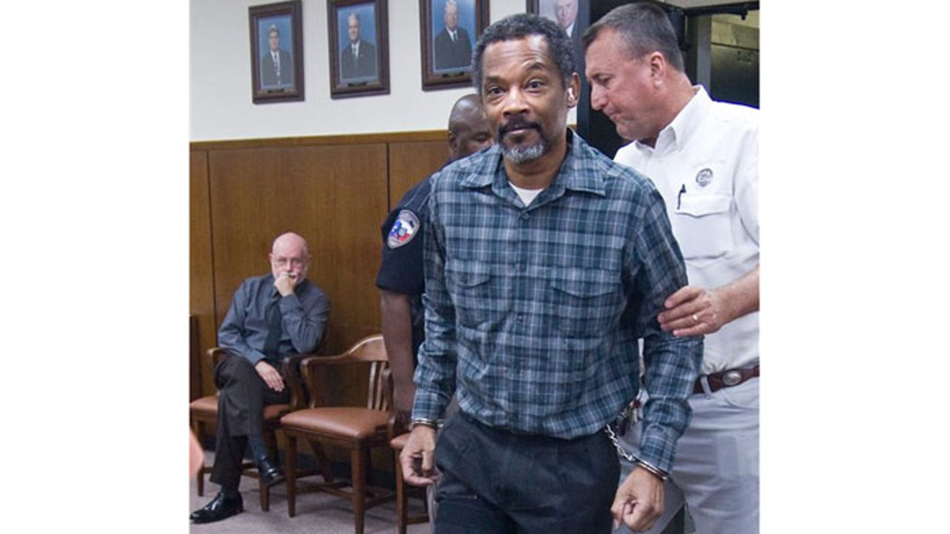 September 13: Defendant Billy Joe Harris enters the Jackson County courtroom in handcuffs and leg shackles in Edna, Texas.