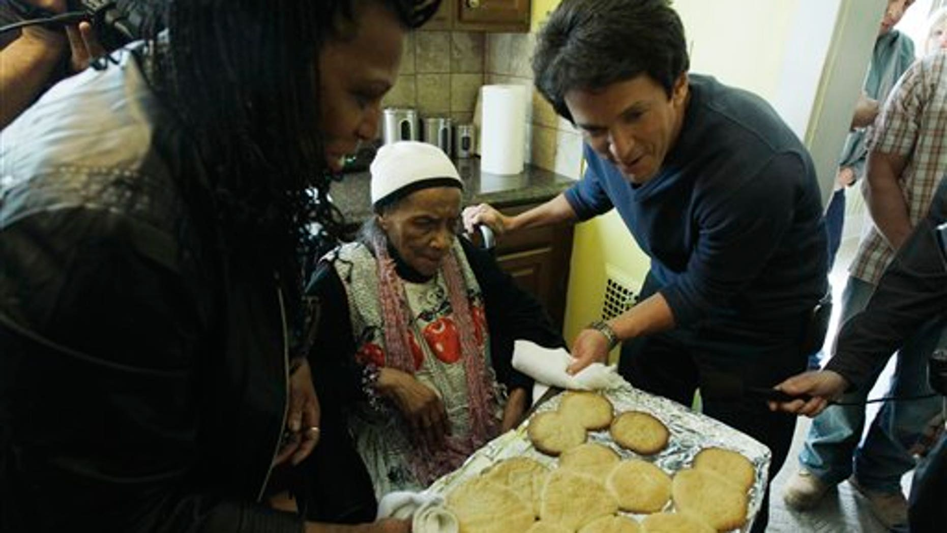 April 4: Detroit Free Press columnist Mitch Albom, right, helps Texana Hollis pull cookies from the oven in her home in Detroit.