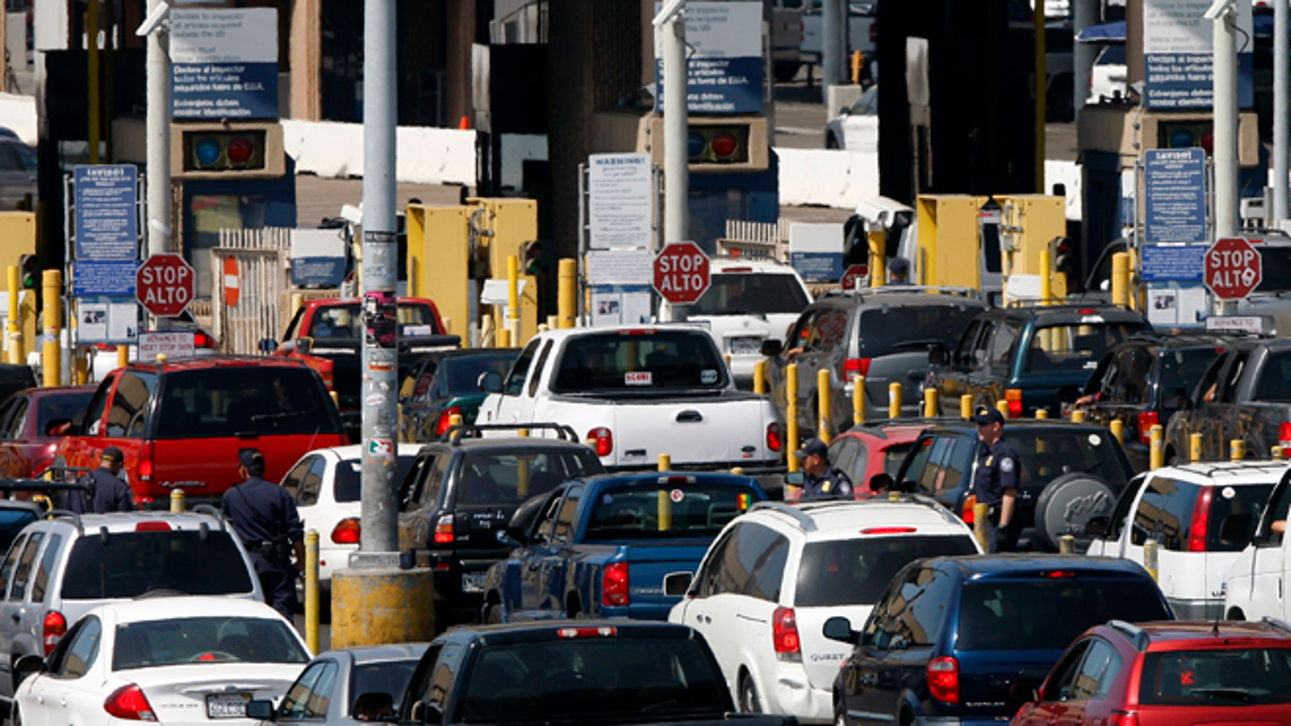 Federal agents mix into a swarm of automobiles as they do security checks  on vehicles waiting to enter the U.S. at the San Ysidro Border Crossing in San Diego, on Sept. 22, 2009.