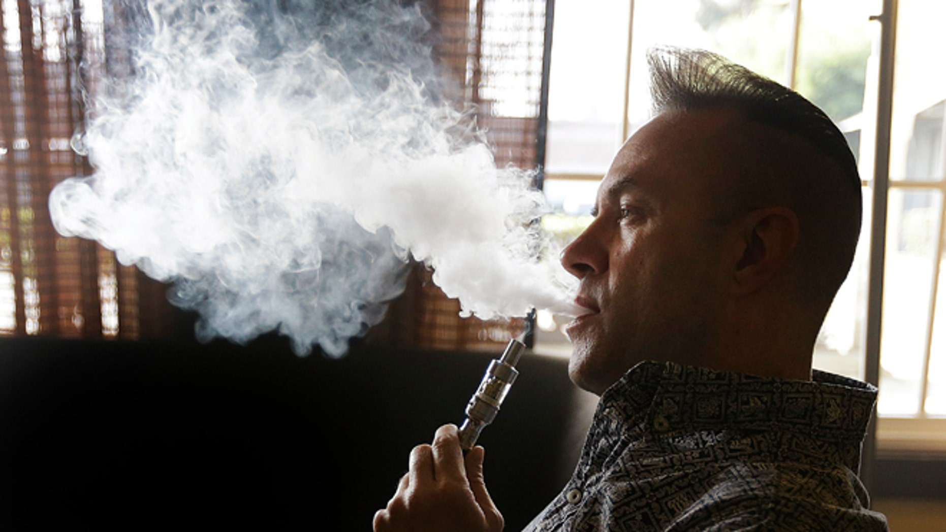 "Geoff Braithwaite, owner of Tasty Vapor, exhales vapor after using an electronic cigarette Wednesday, Jan. 28, 2015, in Oakland, Calif. California health officials on Wednesday declared electronic cigarettes a health threat that should be strictly regulated like tobacco products, joining other states and health advocates across the U.S. in seeking tighter controls as ""vaping"" grows in popularity. The California Department of Public Health report says e-cigarettes emit cancer-causing chemicals and get users hooked on nicotine but acknowledges that more research needs to be done to determine the immediate and long-term health effects. (AP Photo/Ben Margot)"