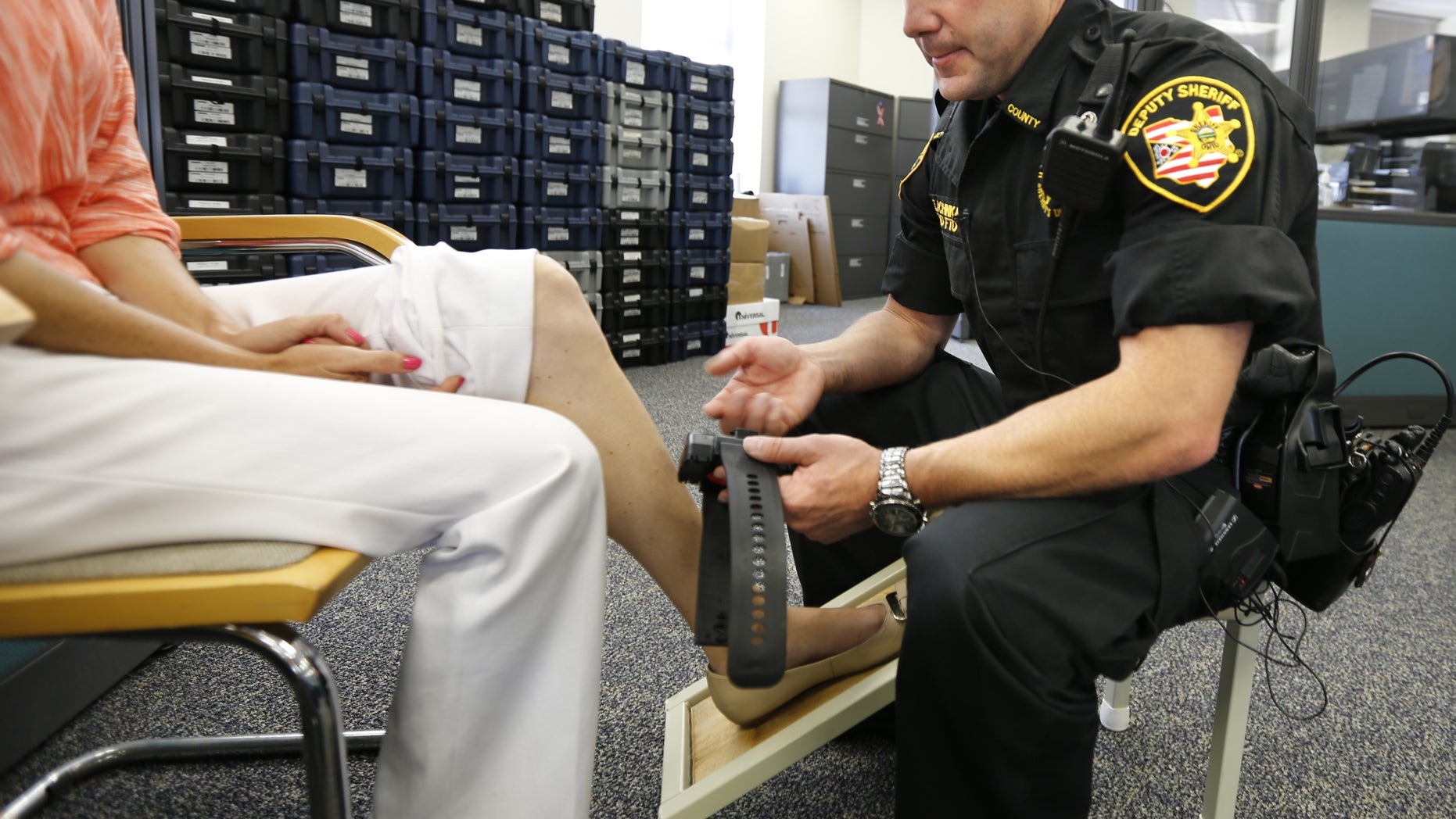 July 12, 2013: Deputy Edward Schinkal attaches an electronic monitoring unit to a woman who was sentenced to home incarceration, in Cincinnati.