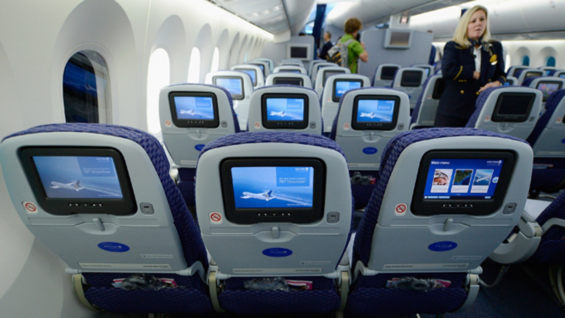 United Airlines flight attendant Tina looks at personal entertainment systems on the new Boeing 787 Dreamliner during a tour of the jet at Los Angeles International Airport on November 30, 2012 in Los Angeles, California. (Photo by Kevork Djansezian/Getty Images)