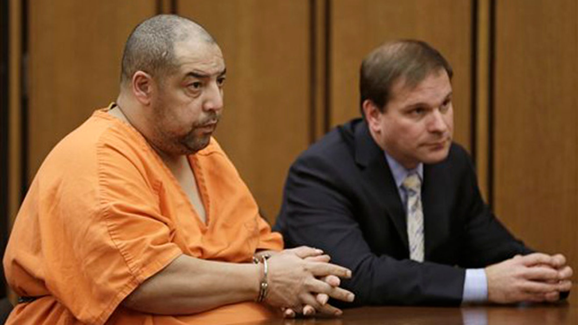 Elias Acevedo, left, looks toward the judge during his pretrial hearing Monday, Dec. 2, 2013, in Cleveland. Acevedo, a convicted sex offender, is charged with two murders and 173 counts of rape. The judge set the trial date for Feb. 24, 2014. Defense attorney Bret Jordan, right, listens. (AP Photo/Tony Dejak)