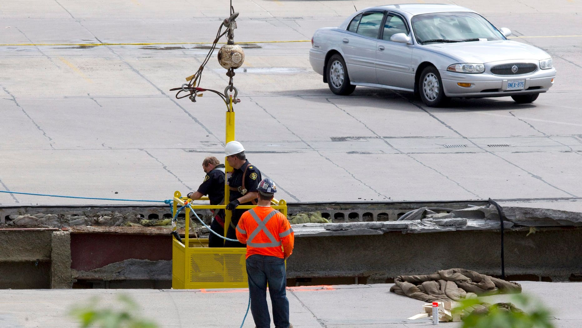 June 25, 2012: OPP officers inspect the damage from the roof as rescue workers continue attempts to secure the building before searching for any survivors at the site of the collapsed roof of the Algo Centre Mall in Elliot Lake, Ontario.