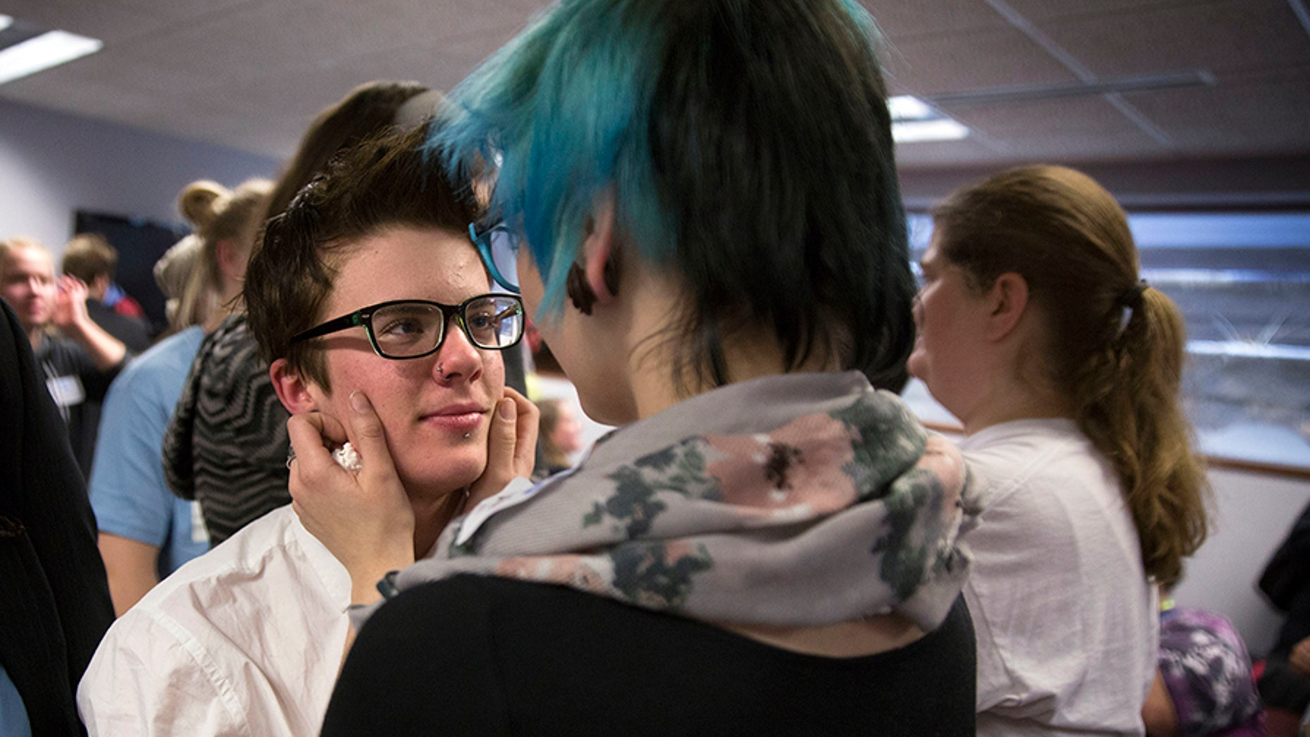 In this Dec. 4, 2014 file photo, Elliott Kunerth, 17, a transgender male high school student hugs his girlfriend, Kelsi Pettit, 17, after the Minnesota State High School League board voted to pass the Model Gender Identity Participation in MSHSL Activities Policy in Brooklyn Park, Minn. (Leila Navidi/Star Tribune via AP)