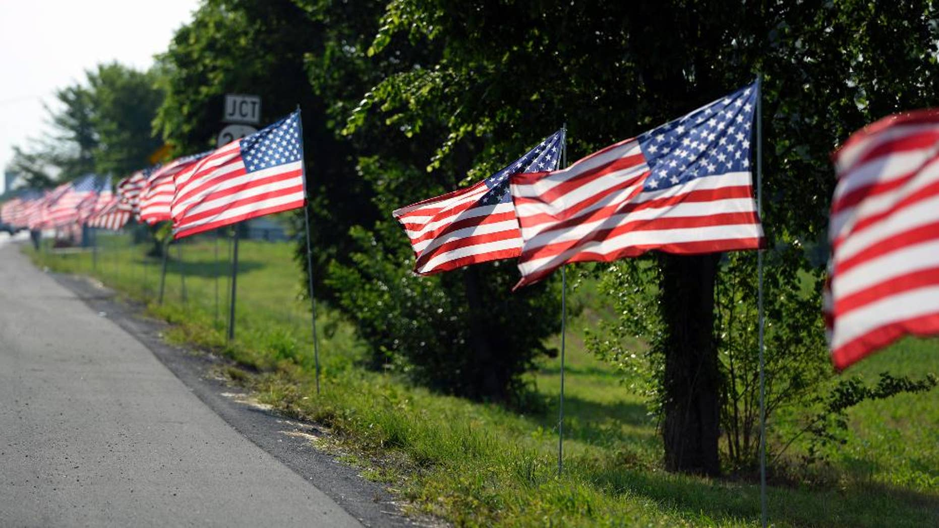 FILE - In this Thursday, May 30, 2013, photo, United States flags line the route of the funeral procession of Bardstown, Ky. Officer Jason Ellis during his funeral service   The shocking murder of the ex-minor league baseball player and father of two young boys still haunts Ellis' colleagues and the town of about 12,000 in Kentucky's bourbon country. In the ensuing months, tips poured in, police dangled about $200,000 in reward money and billboards publicized the case. (AP Photo/Timothy D. Easley, File)