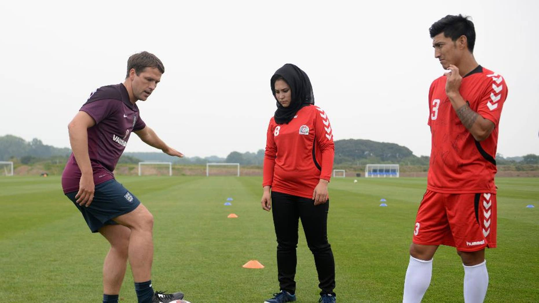 In this image supplied by the Football Association on Monady Sept. 15, 2014  former England international soccer star  Michael Owen. left,  coaches  Afghanistan captain Islamuddin Amiri , right, and an unidentified female member of the delegation from the Afghanistan FA during the  training session at St Georges Park on  Friday Sept. 5, 2014 in Burton-upon-Trent, England. The paths that took Wayne Rooney and Islamuddin Amiri into football couldn't have been more different. When a 9-year-old Rooney was catching the eye of talent spotters in Liverpool in 1995 and joining up with Premier League club Everton, Amiri was enduring hardship and horror under Taliban rule in Kabul, where Afghanistan's national stadium was used for public executions and brutal punishments.  (AP Photo/Michael Regan/The FA) NO ARCHIVE