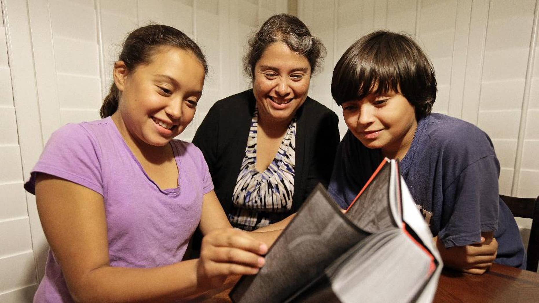 In this Nov. 10, 2014 photo, Rosaisela Rodriguez, center, reads with her children Isabel Gutierrez, left, and Rafael Gutierrez, at their home in Pleasant Hill, Calif. Rodriguez deliberately didn't declare that her twin son and daughter knew Spanish when she enrolled them in school, adding that most 5-year-olds are language learners, regardless of whether they are bilingual. (AP Photo/Ben Margot)