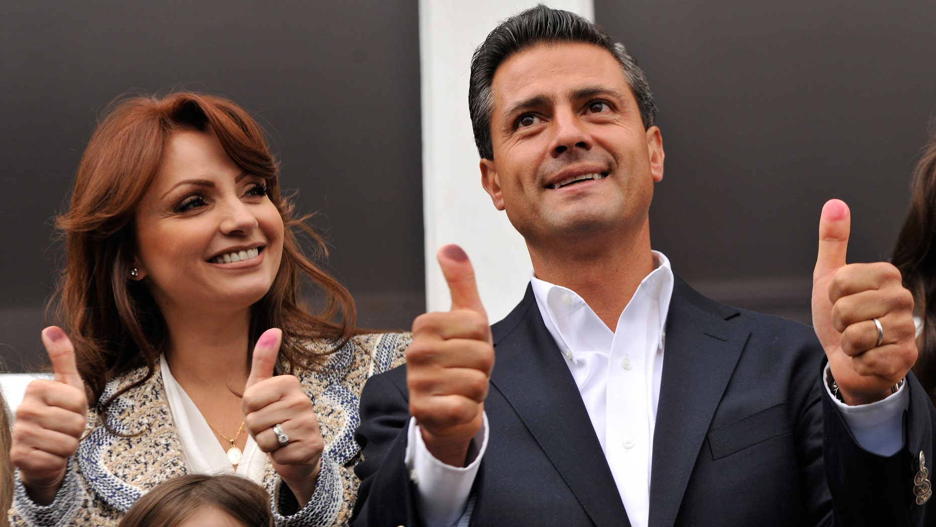 ATLACOMULCO, MEXICO - JULY 1:  Presidential candidate Enrique Pena Nieto of the Institutional Revolutionary Party (PRI), gesutres as he casts his vote with his wife Angelica Rivero de Pena on July 1, 2012 in Atlacomulco, Mexico. Mexicans went to the polls to choose a new president and vote in thousands of state and local posts nationwide. (Photo by Daniel Aguilar/Getty Images)