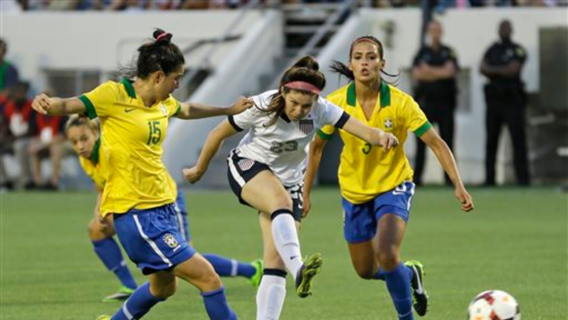 U.S. midfielder Erika Tymrak, center, scores a goal between Brazil midfielder Bia (15) and defender Calandrini (3) during the second half of an international friendly soccer match in Orlando, Fla., Sunday, Nov. 10, 2013. United States Women's national team defeated Brazil 4-1. (AP Photo/John Raoux)