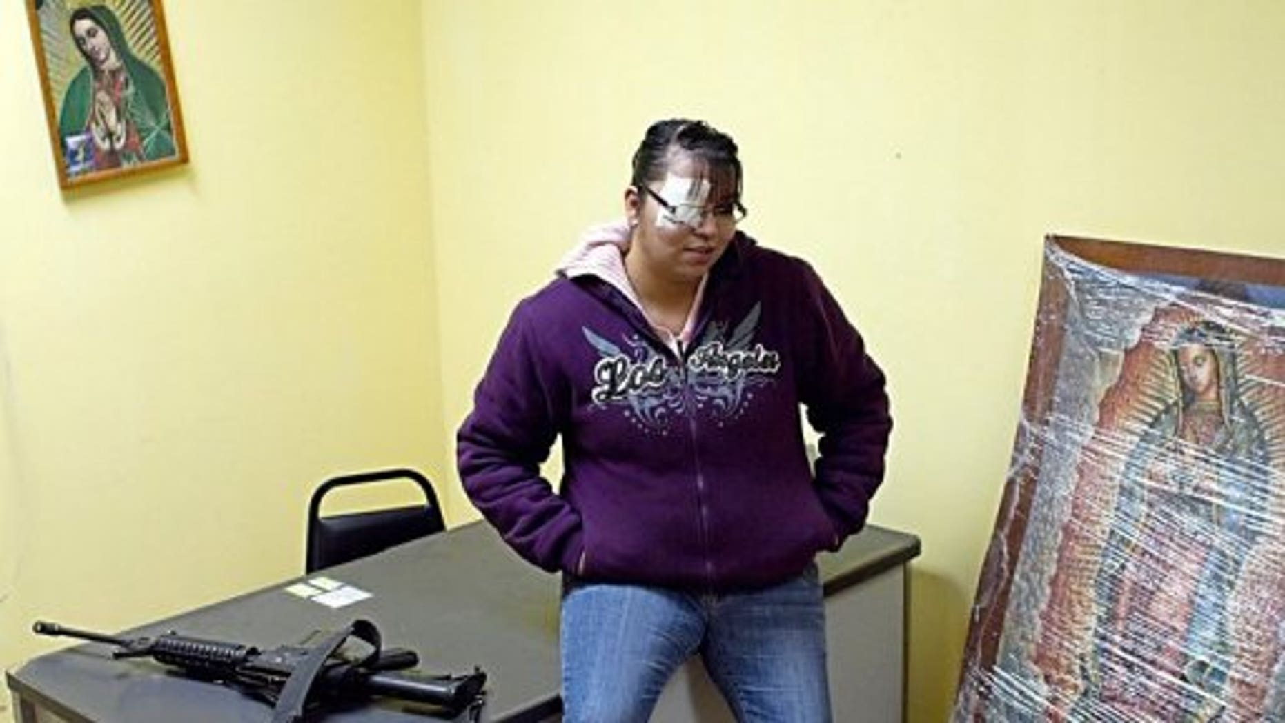 Erika Gandara is seen next to an AR-15 semi-automatic rifle at the police station in Guadalupe.