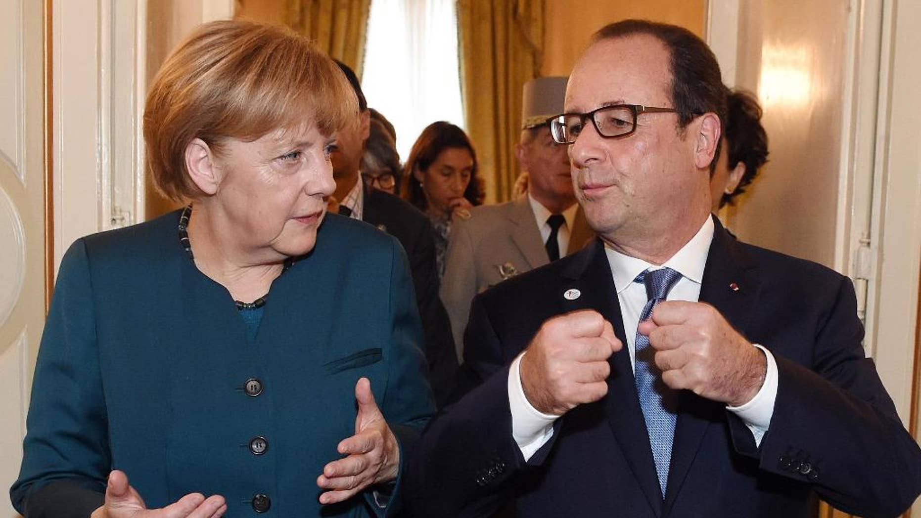 German Chancellor Angela Merkel, left, and French President Francois Hollande talk after a meeting on the sidelines of the  ASEM summit of European and Asian leaders in Milan, northern Italy, Friday, Oct. 17, 2014. Russian President Vladimir Putin is looking to get relief from Western economic sanctions imposed since Russia's annexation of the Crimean Peninsula and its support for a pro-Russia insurgency in eastern Ukraine. To that end, he has scheduled a series of meetings on the sidelines of a two-day ASEM summit of European and Asian leaders. (AP Photo/Daniel Dal Zennaro, POOL)