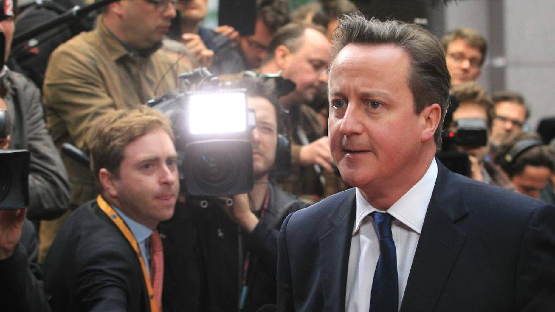 FILE - In this Tuesday, May 27, 2014 file photo, British Prime Minister David Cameron walks past the media upon arrival at the European Council building in Brussels. Many political battles are ugly _ but toss in 28 nations, high unemployment, angry voters and a skeptical Britain and the fight over who will be the European Union's next chief executive may have downright hideous consequences. Britain's Prime Minister David Cameron has set himself up for a stinging defeat as his vocal campaign to block the front-runner for the top EU job, former Luxembourg prime minister and longtime Brussels insider Jean-Claude Juncker, fails to gain traction. (AP Photo/Yves Logghe, File)
