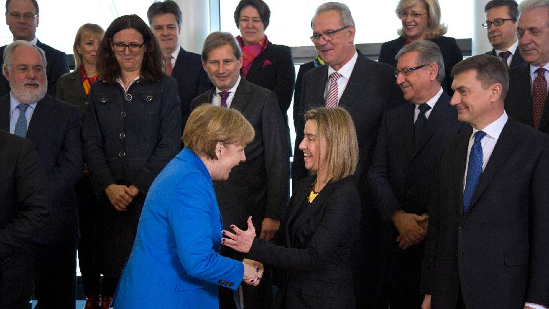 German Chancellor Angela Merkel, center left, is greeted by European Union High Representative Federica Mogherini, center right, during during a group photo of the College of Commissioners at EU headquarters in Brussels on Wednesday, March 4, 2015. (AP Photo/Virginia Mayo)