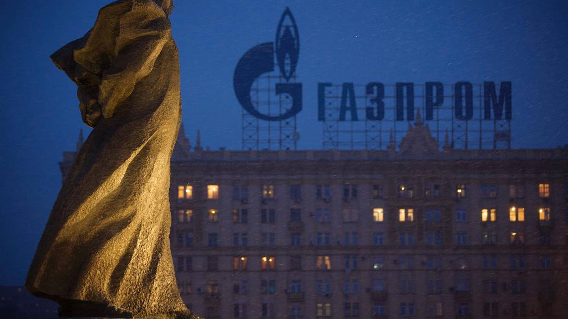 """FILE - In this Tuesday, March 4, 2014 file photo, a monument to Ukrainian poet and writer Taras Shevchenko is silhouetted against an apartment building with a sign advertising Russia's natural gas giant Gazprom, in Moscow, Russia. Poland has resumed deliveries of gas to Ukraine that it had halted after its own supplies from Russia dropped this week, the state pipeline operator said Friday, Sept. 12, 2014. The statement by Gaz-System S.A. suggests gas flows from Russian supplier Gazprom are once again meeting Poland's daily demand. State gas company, PGNiG, said that on Thursday it still registered some deficit compared to the ordered amount, but that the shortfall was lower than on Wednesday, when supplies were 45 percent short of demand. The spat between Poland and Russia came amid concerns that Moscow is ready to use its energy exports as a political weapon over the crisis in Ukraine.""""We do not treat the situation as a crisis,"""" Zawisza said. """"It is just one incident."""" (AP Photo/Alexander Zemlianichenko, file)"""