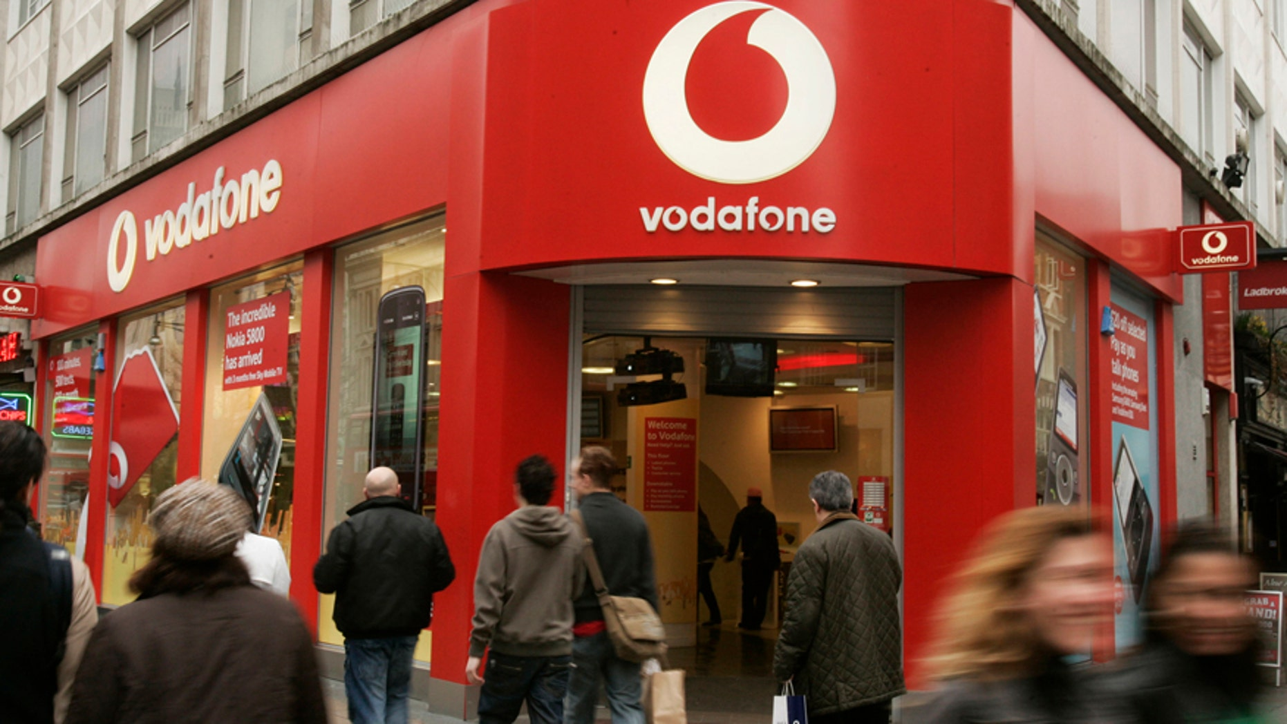 This Tuesday, Feb. 24, 2009 file photo shows people walking by a branch of Vodafone in central London.