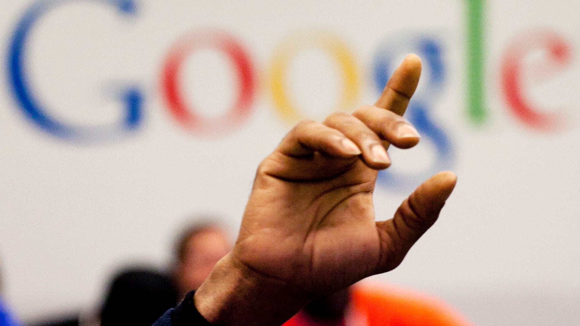 FILE - In this Oct. 17, 2012, file photo, a man raises his hand during at Google offices in New York. People should have some say over the results that pop up when they conduct a search of their own name online, Europe's highest court said Tuesday, May 13, 2014. (AP Photo/Mark Lennihan, File)