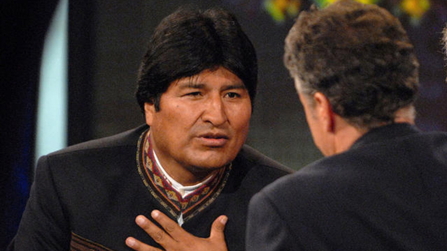 "Bolivian President Evo Morales, left, speaks with Daily Show host Jon Stewart, center, on Comedy Central's ""The Daily Show with Jon Stewart"" in New York, Tuesday Sept. 25, 2007. Morales's translator is seen at right. (AP Photo/Peter Kramer)"