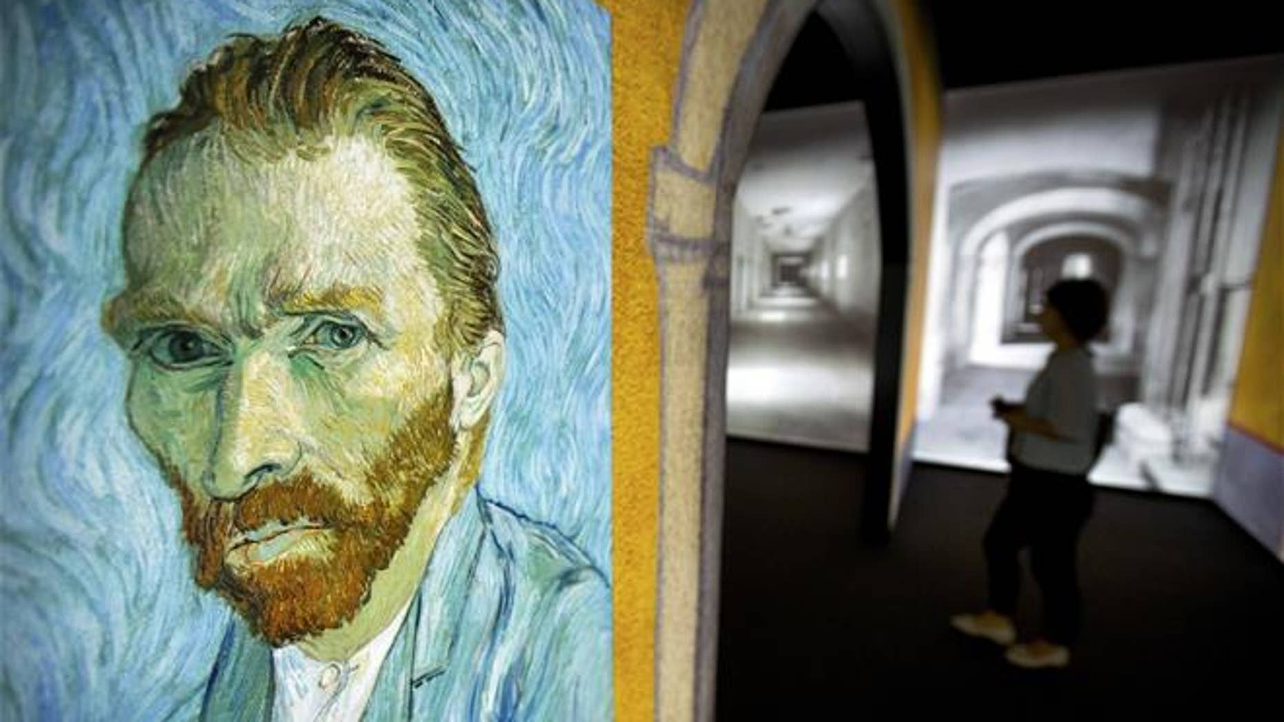 """A visitor walks past an image of Van Gogh's """"Self-Portrait"""" during a press event for the world premiere of the """"Meet Vincent Van Gogh"""" exhibit in Beijing on June 15, 2016."""