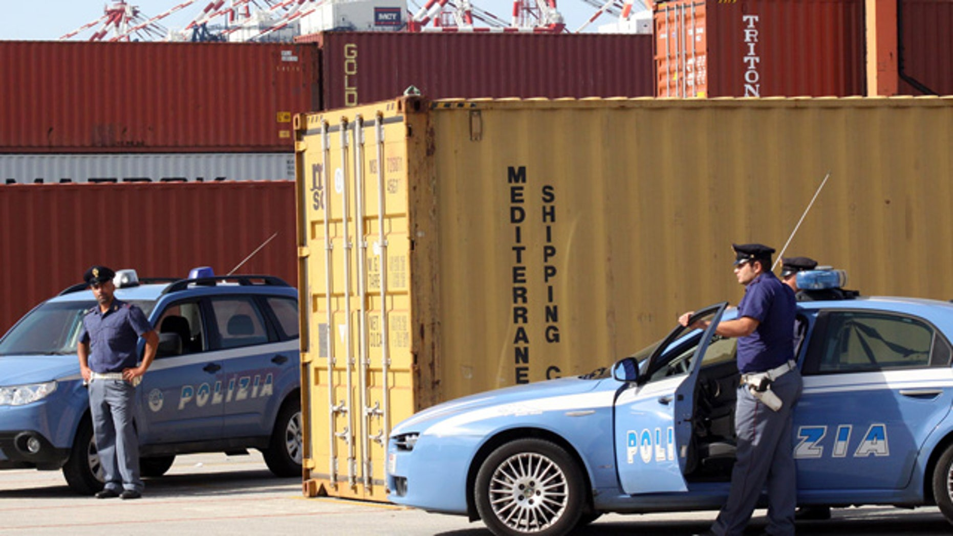 """Italian police stand guard by a confiscated container, in the port of Gioia Tauro, near Reggio Calabria, southern Italy, on Wednesday,  Sept. 22, 2010. Police officials say they have seized a """"huge'' shipment of powerful RDX explosives that may have originated in Iran. Reggio Calabria police chief Carmelo Casabona told an Italian private television news that the amount was too large to be destined only to the Calabrian mob. (AP Photo/Adriana Sapone)"""