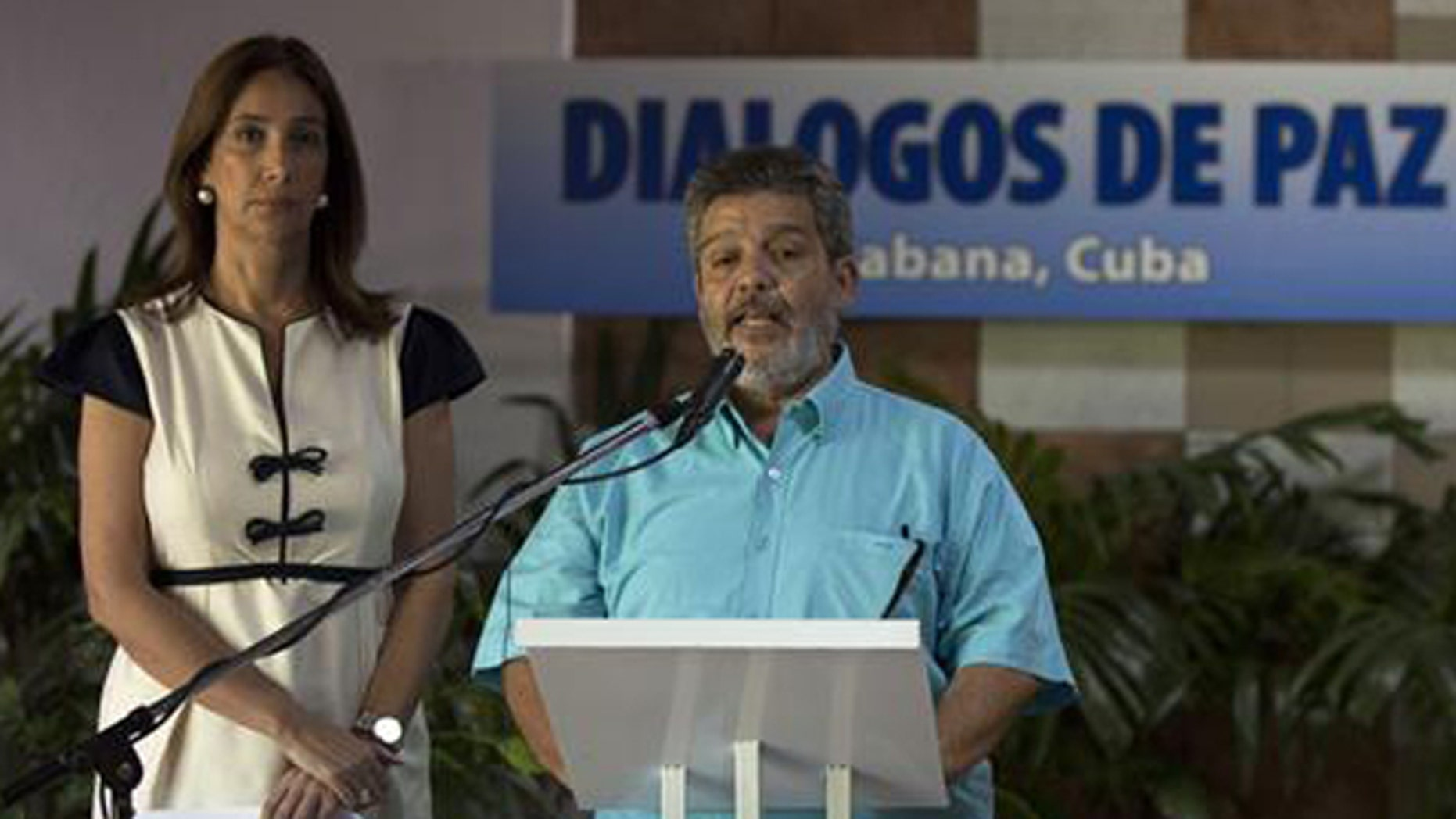 Accompanied by Marcela Duran, left, the Colombian government delegation's head of press, Marco Leon Calarca, member of the Revolutionary Armed Forces of Colombia, or FARC, speaks during the announcement of a deal on bilateral cease-fire that would be the last major step toward ending one of the world's longest wars, in Havana, Cuba, Wednesday, June 22, 2016. (Cubadebate via AP)