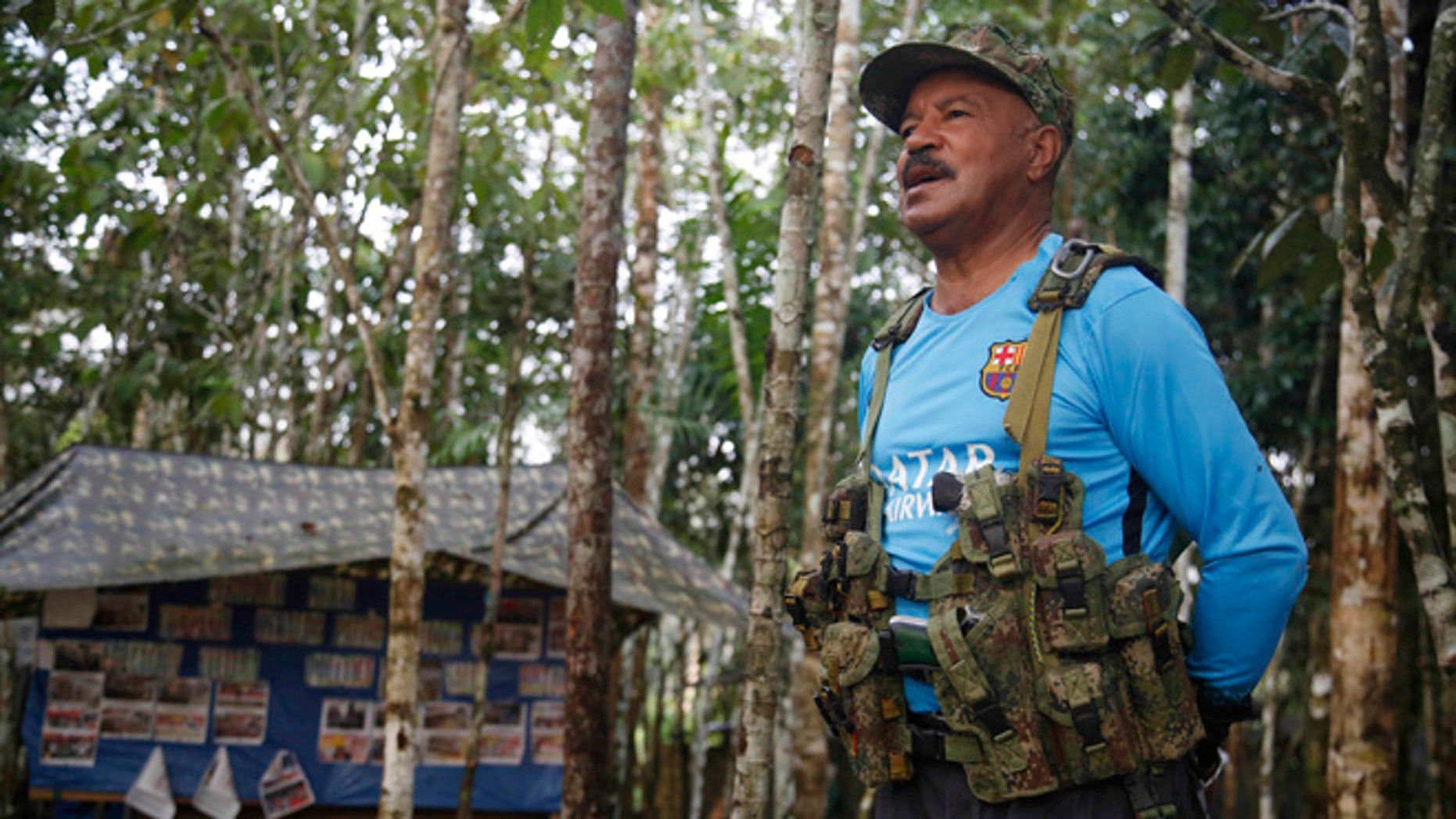 In this Wednesday, Aug. 17, 2016 photo, Martin Corena, acting commander of the Revolutionary Armed Forces of Colombiaââ¬â¢s southern bloc, FARC, addresses his troops in the southern jungles of Putumayo, Colombia. Corena is calling on President Barack Obama to free a guerrilla leader jailed for more than a decade in the U.S. Corena said Ricardo Palmeraââ¬â¢s 60-year sentence in connection to the FARCââ¬â¢s holding captive of three American defense contracts was incompatible with Obamaââ¬â¢s support for a peace deal. (AP Photo/Fernando Vergara)