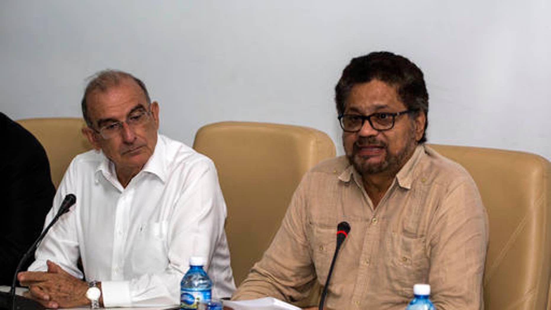 Humberto de La Calle, left, head of Colombia's government peace negotiation team, listens as Ivan Marquez, chief negotiator of the Revolutionary Armed Forces of Colombia (FARC) reads a joint statement in Havana, Cuba, Friday, Oct. 28, 2016. The statement said many new proposals have been incorporated in the text of a new peace accord after voters narrowly defeated the deal on Oct. 2.  (AP Photo/Desmond Boylan)