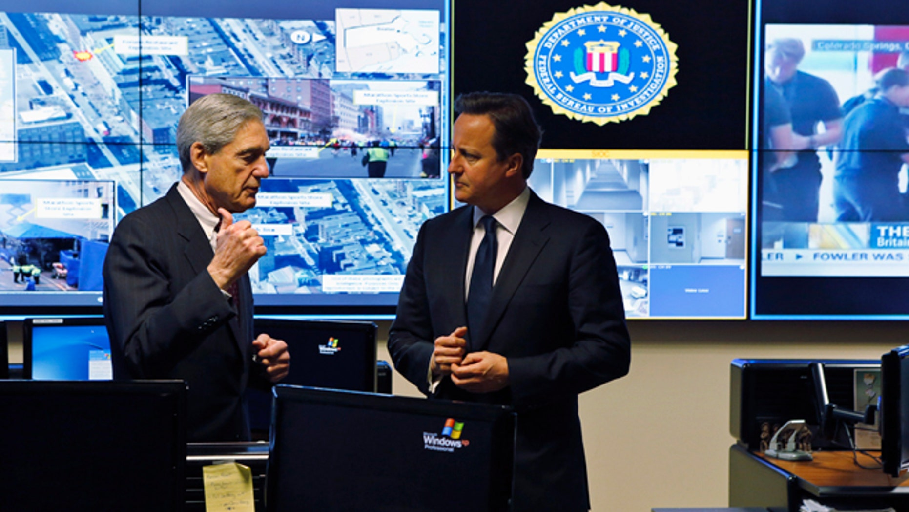 FILE: May 13, 2013: FBI Director Robert Mueller (L) and Britain's Prime Minister David Cameron at the Strategic Information Operations Center at the FBI headquarters in Washington, D.C.
