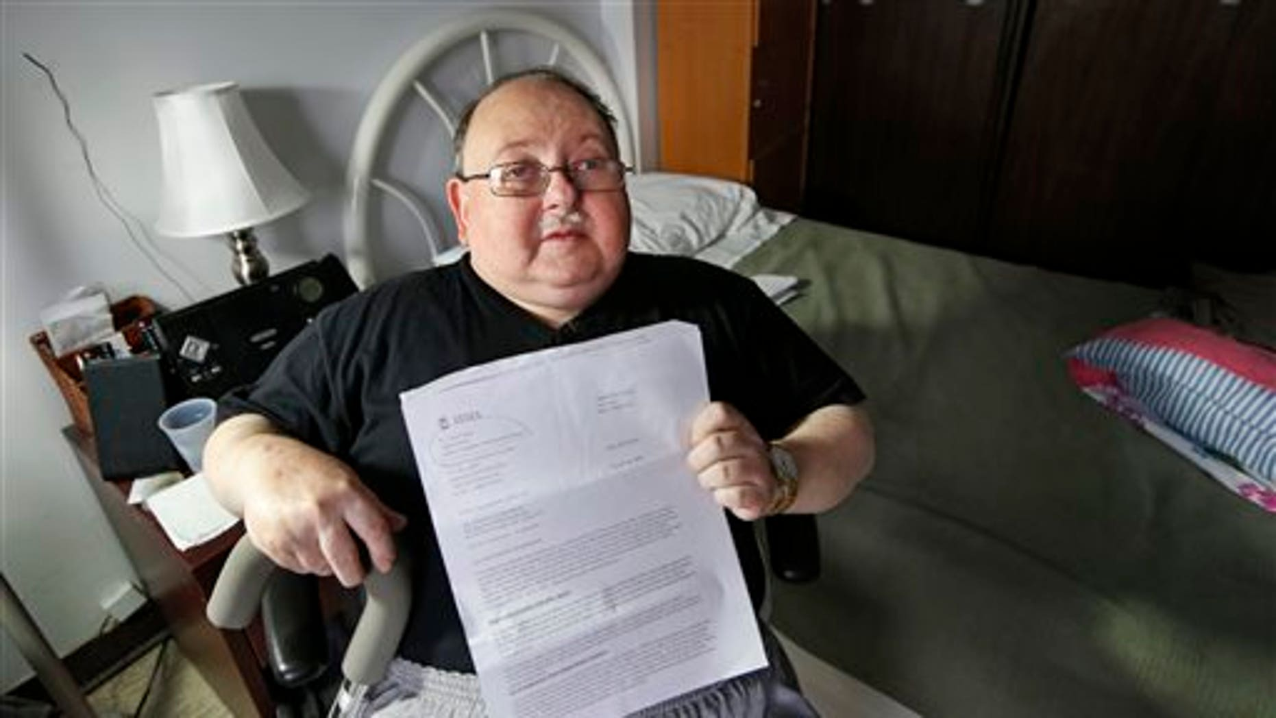 Belle Harbor Manor resident Robert Rosenberg, 61, who suffers from a spinal disability and has other chronic health problems, sits in his room in an assisted living facility in New York, Thursday, Nov. 6, 2014, where he and elderly, poor and disabled residents endured four months of misery after Superstorm Sandy flooded the center, located on New York's vulnerable Rockaway peninsula. Rosenberg holds a letter from the Federal Emergency Management Agency (FEMA) asking him to pay back all the federal disaster aid he received after the storm. He is among a dozen residents of Belle Harbor Manor who have been asked to return aid money.  (AP Photo/Kathy Willens)