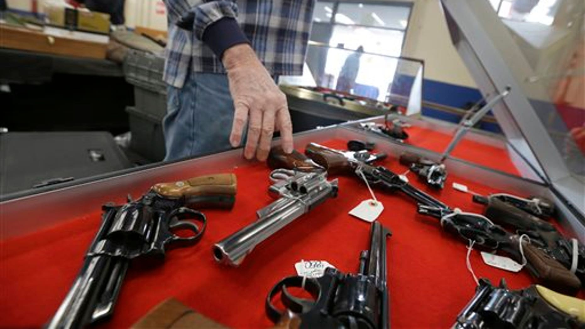 In this Friday, Feb. 6, 2015 photo, a dealer arranges handguns in a display case in advance of a show at the Arkansas State Fairgrounds in Little Rock, Ark. Arkansas gun advocates in the Legislature are supporting bills that would permit firearms on university campuses, expanding citizens' rights to use deadly force and other efforts. (AP Photo/Danny Johnston)