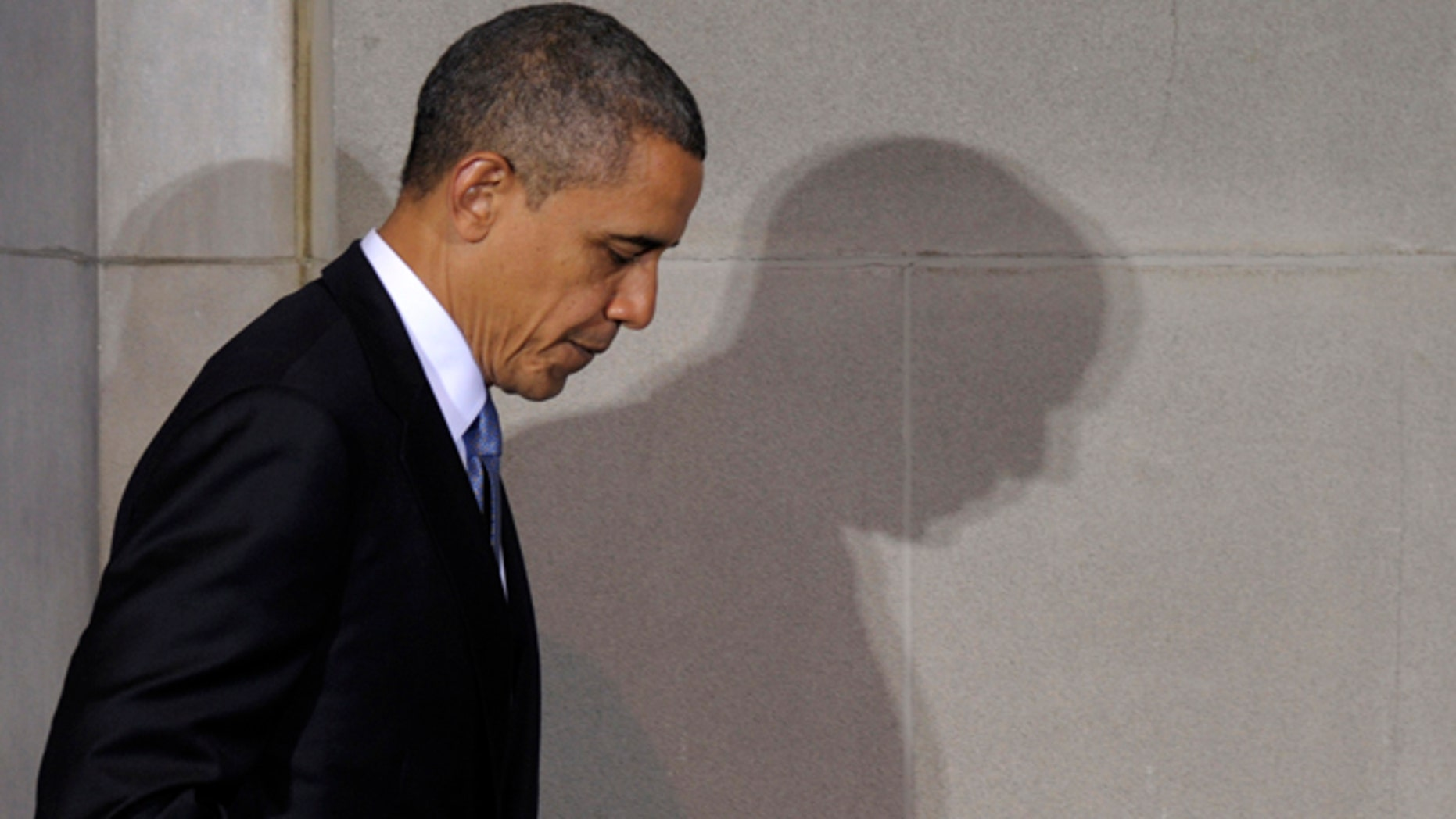"""President Barack Obama casts a shadow as he walks off of the stage after speaking at the 2012 Tribal Nations Conference, Wednesday, Dec. 5, 2012, at the Interior Department in Washington. Native American tribal leaders are concerned that steady progress on their issues might be undermined if President Barack Obama and Congress make deep spending cuts to avoid the """"fiscal cliff.""""  More than 500 tribal leaders were taking those concerns to the fourth White House Tribal Nations summit, which convenes Wednesday. (AP Photo/Susan Walsh)"""