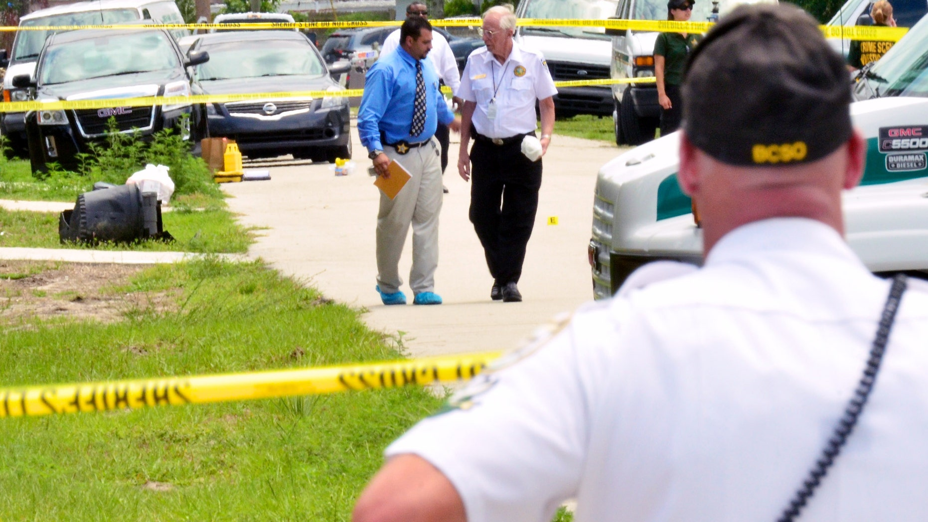 PORT ST JOHN, FL - MAY 15:  Brevard County crime scene workers conduct an investigation after Tonya Thomas shot her four children and then herself May 15, 2012 in Port St. John, Florida. The children ranged in ages 12 to 17 and the family had a history of domestic complaints.  (Photo by Roberto Gonzalez/Getty Images)