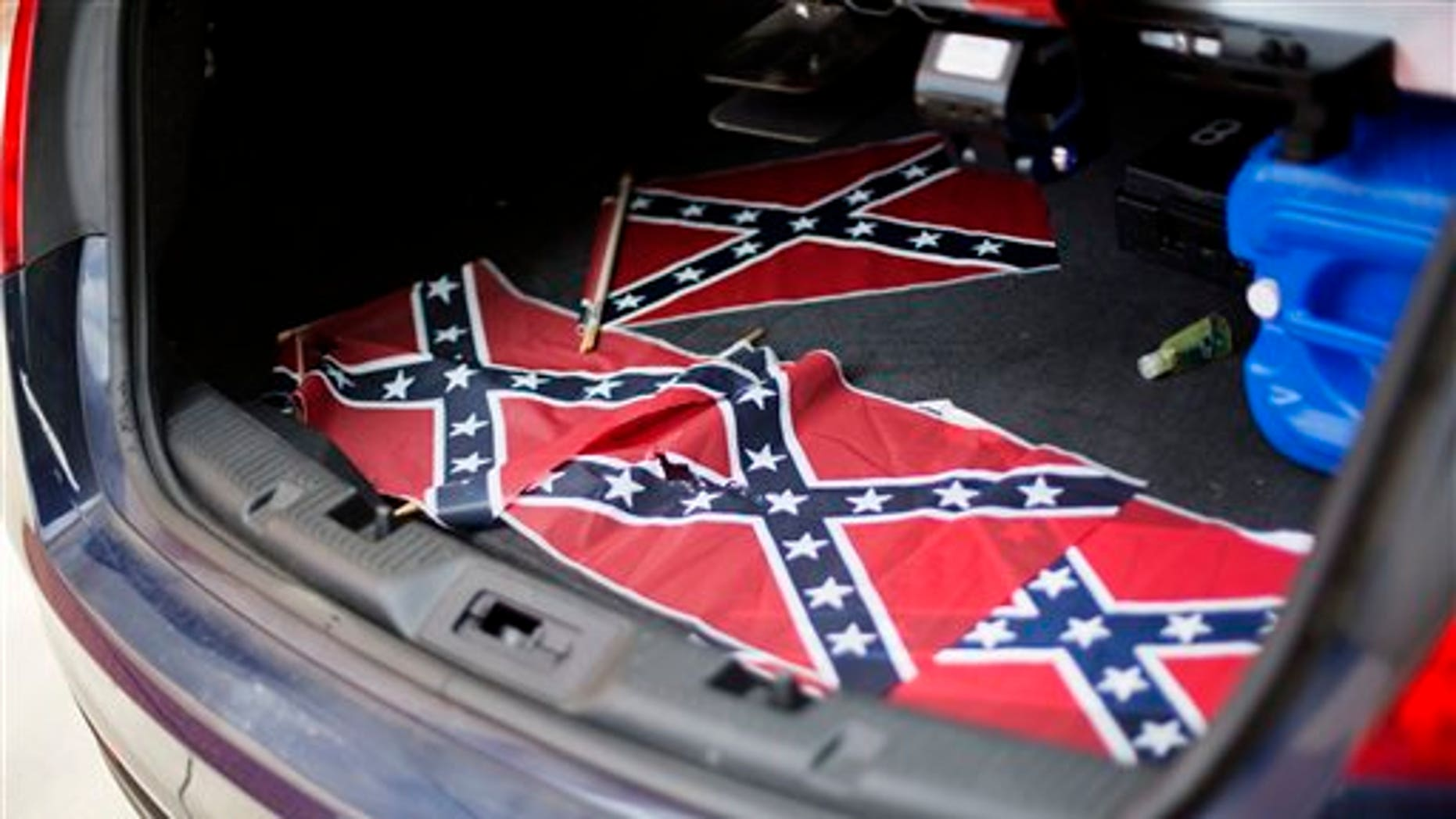 Confederate flags sit in the back of a police car outside Ebenezer Baptist Church Thursday, July 30, 2015, in Atlanta. U.S. authorities are investigating after several Confederate battle flags were discovered near the church and a civil rights center named after Martin Luther King, an iconic leader in the African-American Civil Rights Movement, Thursday morning. (AP Photo/David Goldman)