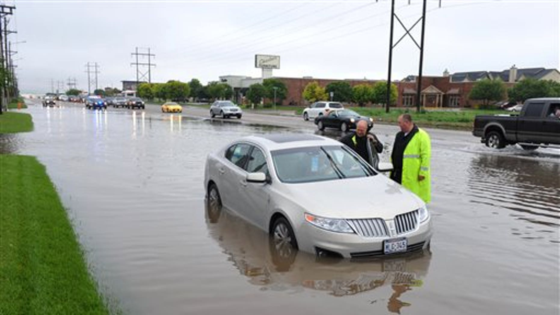 May 23, 2015: Amarillo, Texas, police officers make an emergency water rescue of a stranded motorist after heavy rain showers flood much of the city.